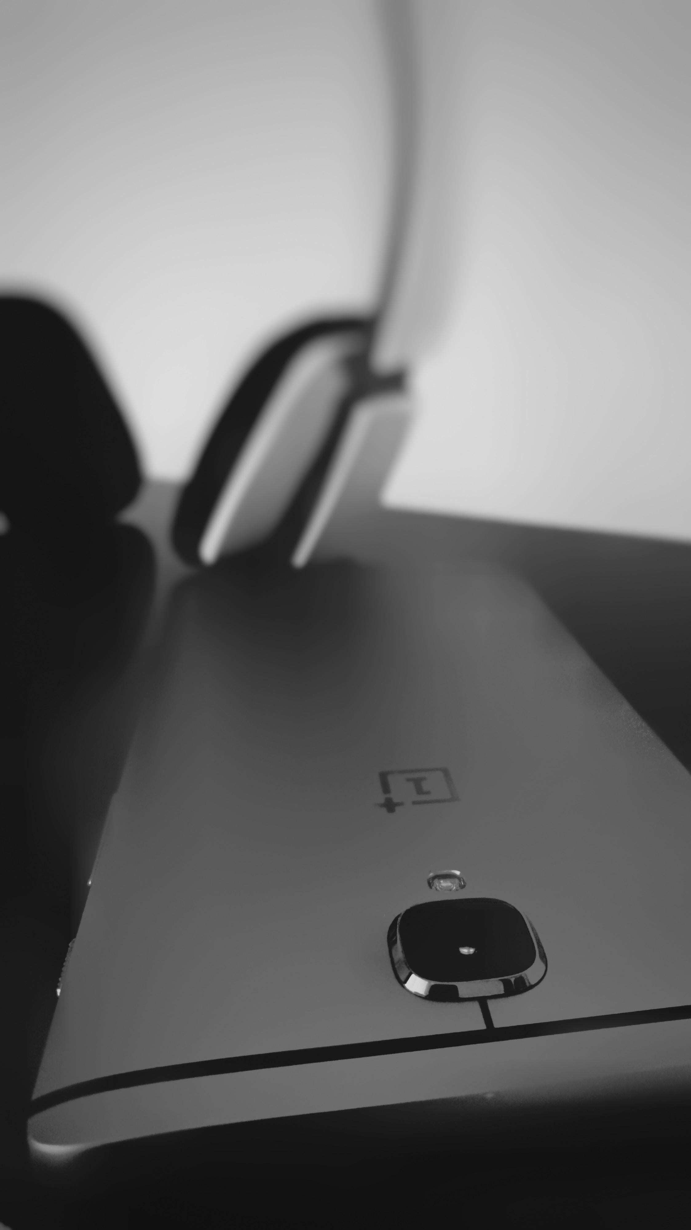 A black smartphone near headphones.