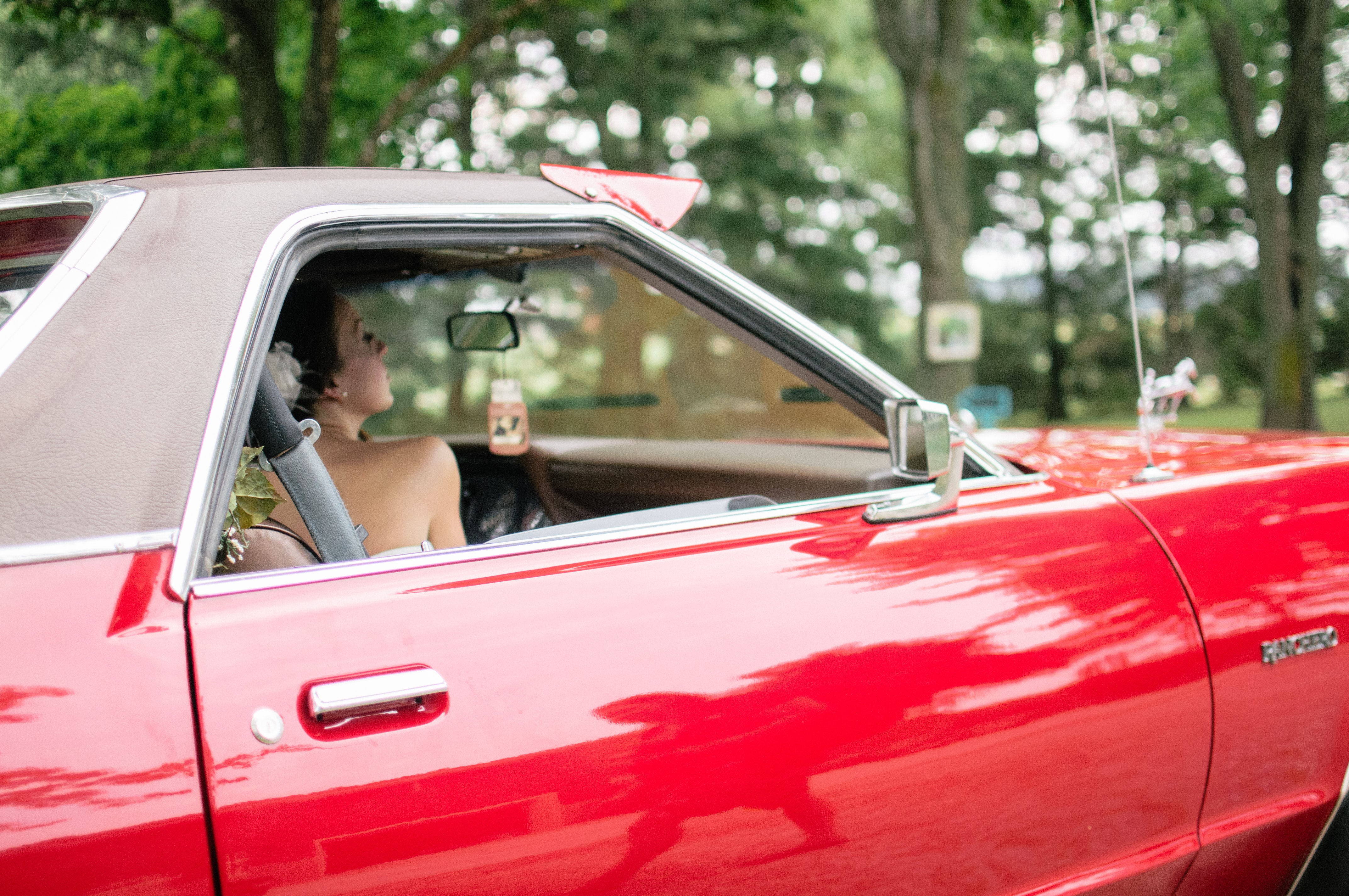 woman riding on red coupe