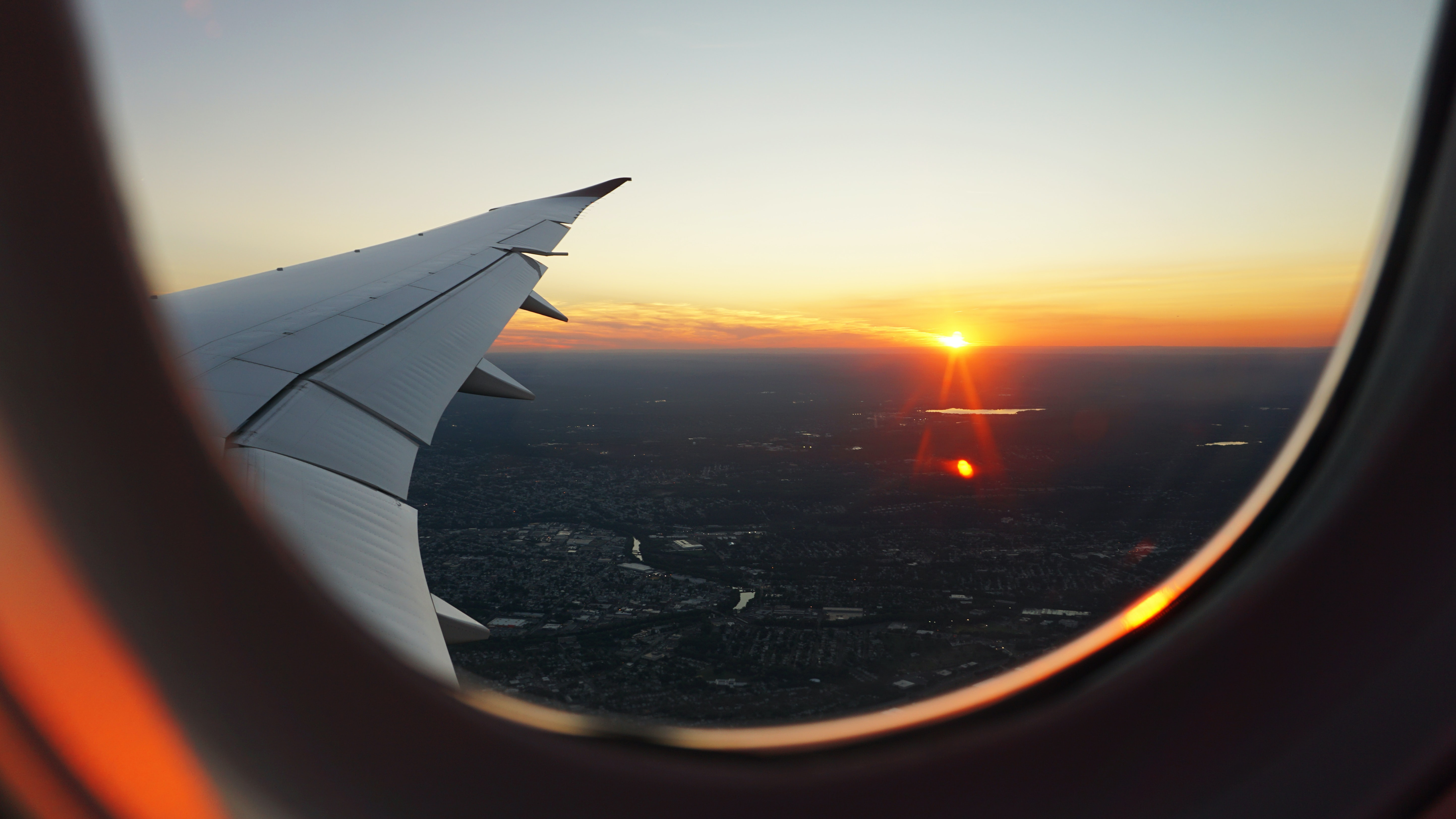 A view from an airplane window on the sun setting on the horizon
