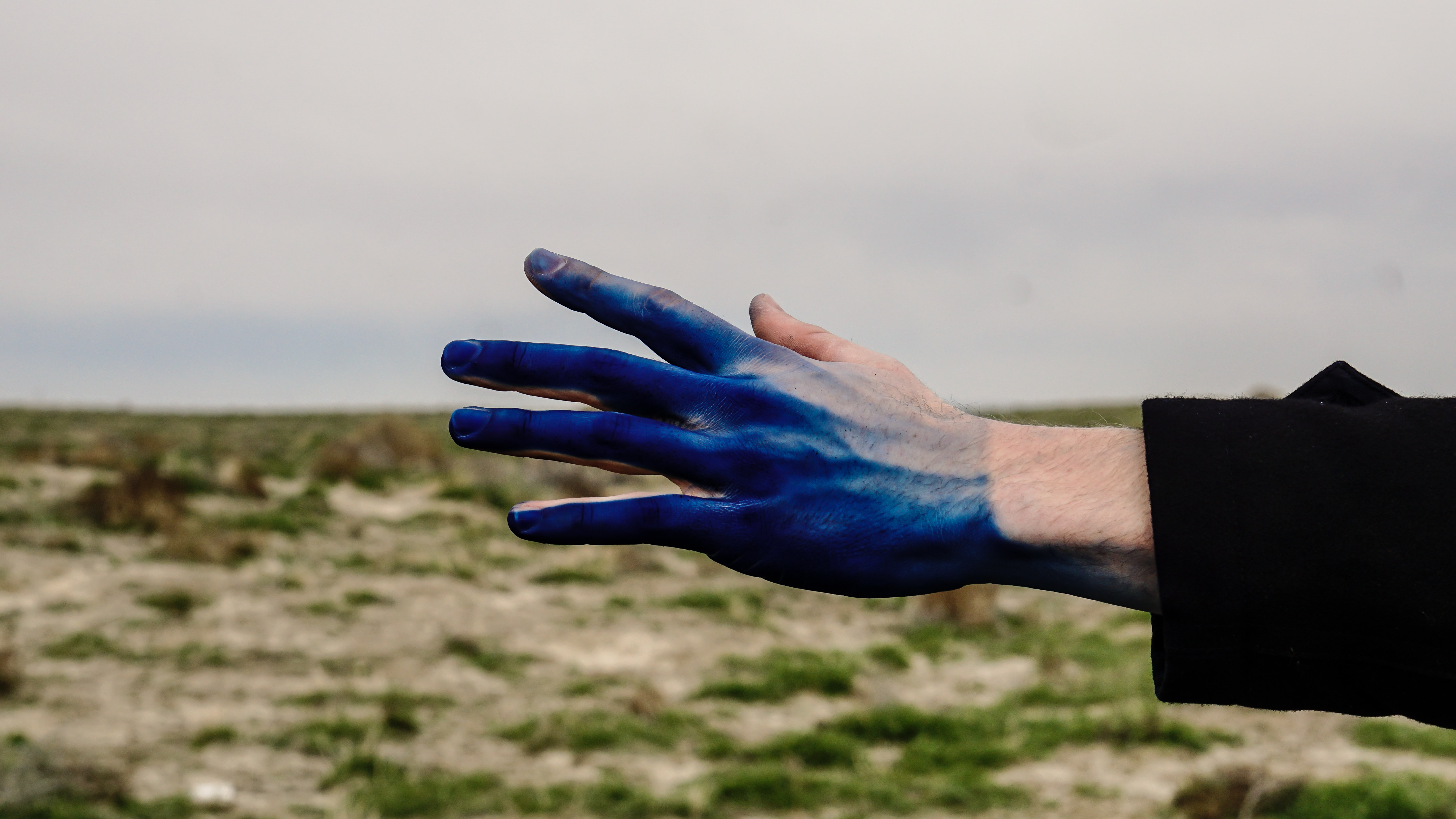 A person reaching out with their blue paint covered hand.