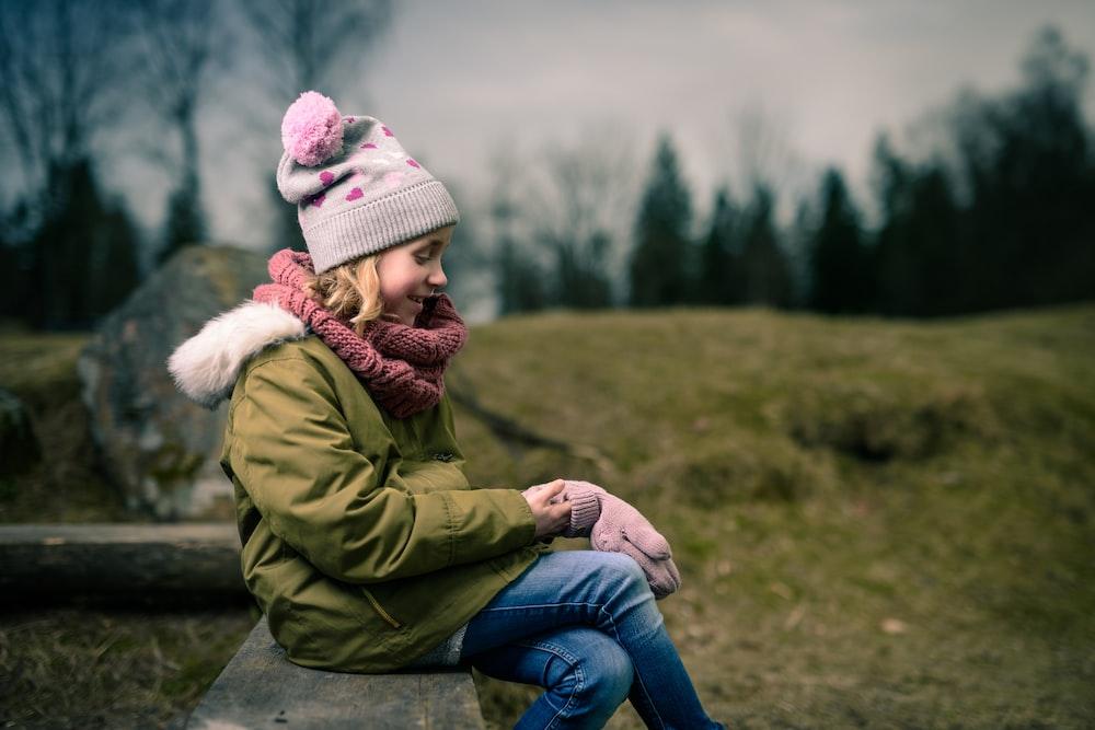 smiling girl sitting on brown bench