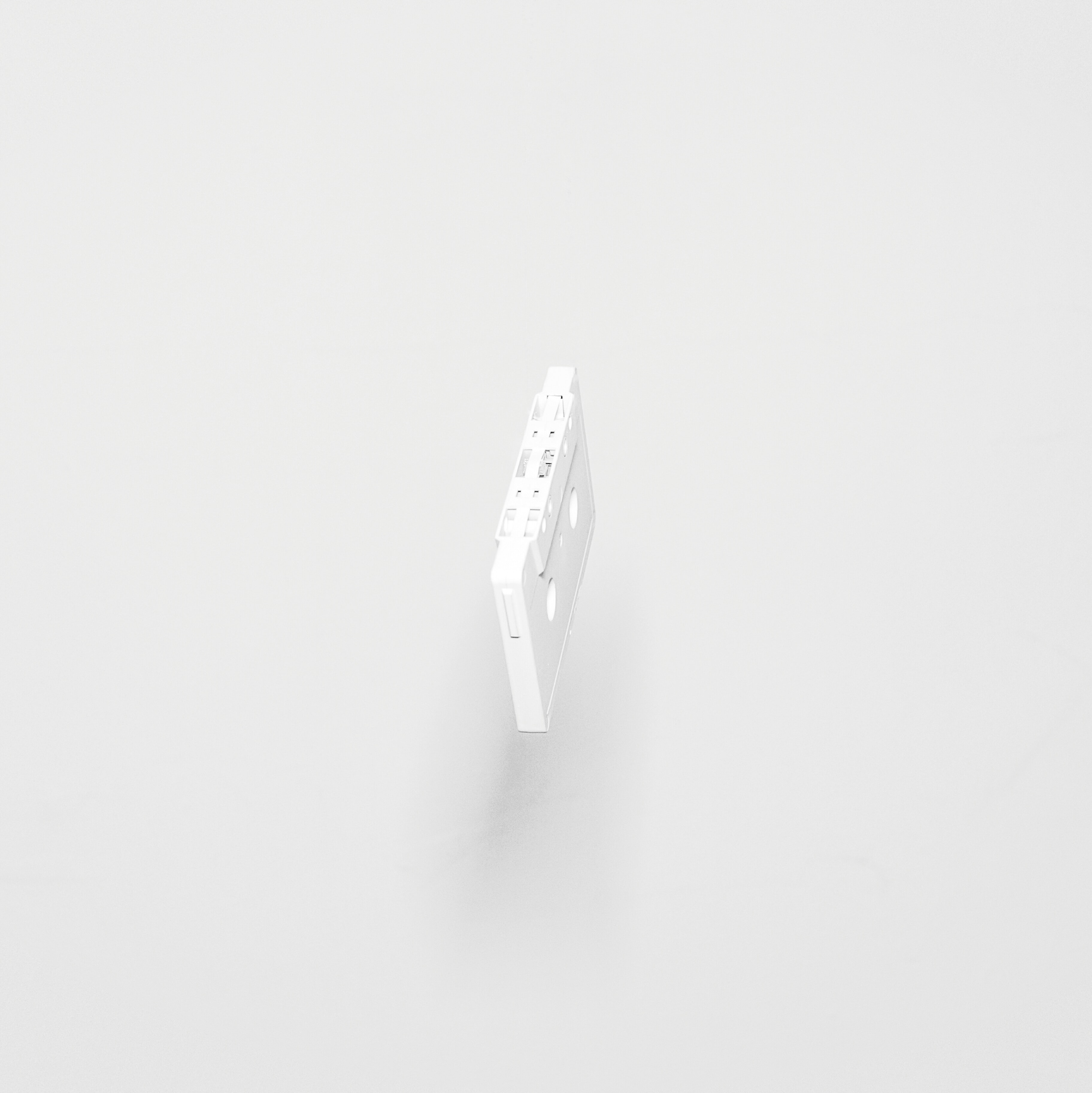 A white cassette tape suspended in the air above a white surface