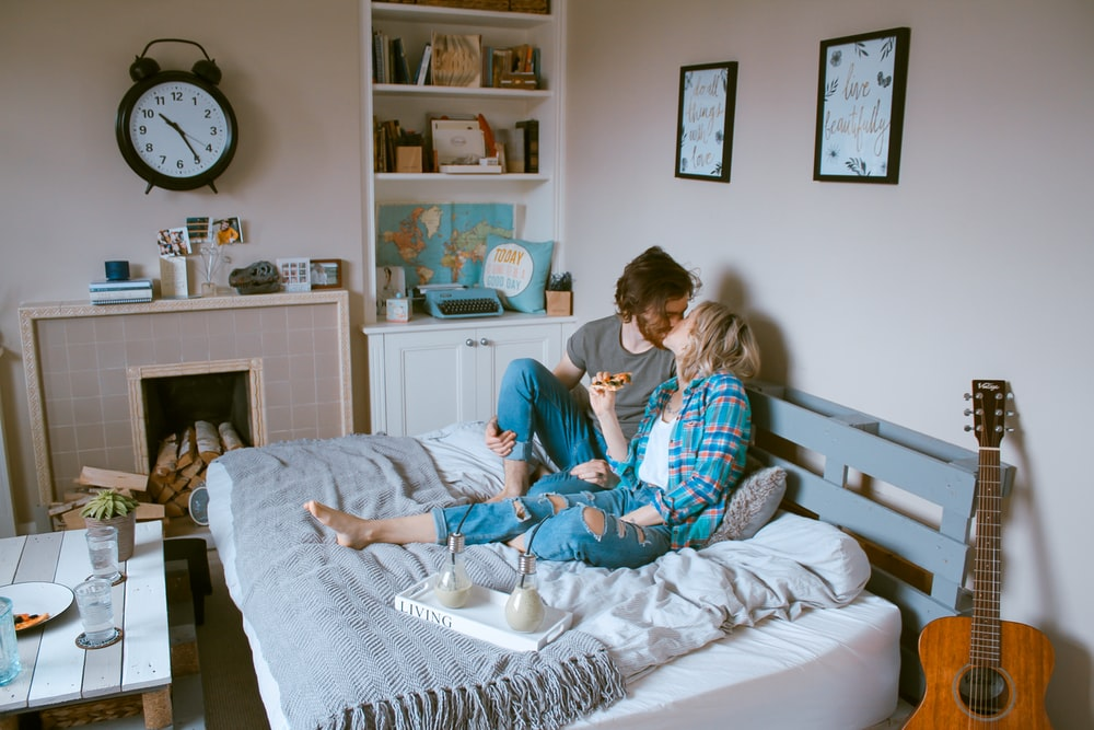man and woman kissing on bed