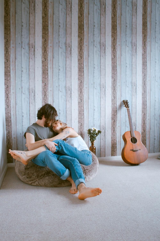 man and woman sitting on gray beanbag