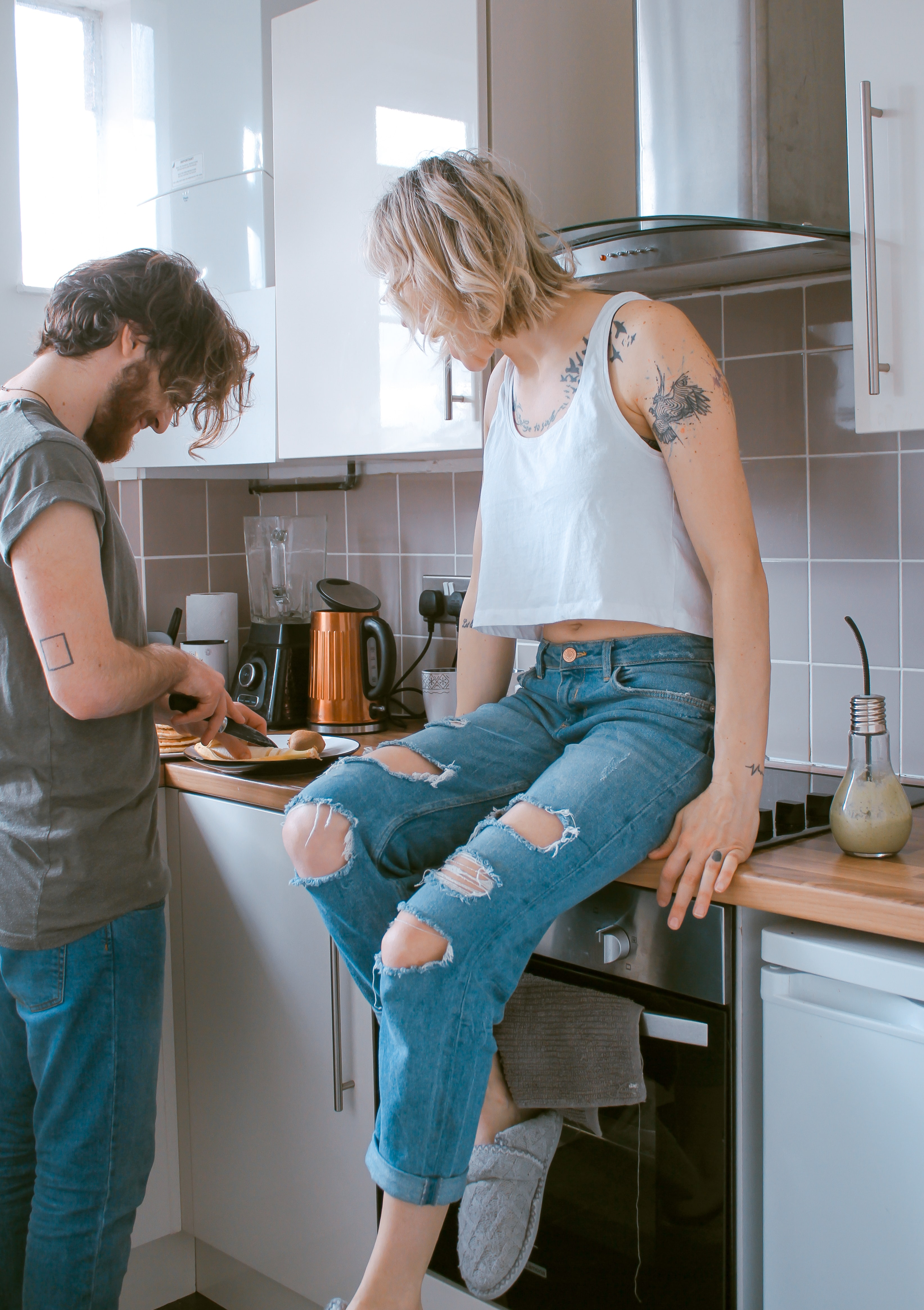 A woman sitting on the kitchen counter while watching a man prepare food.