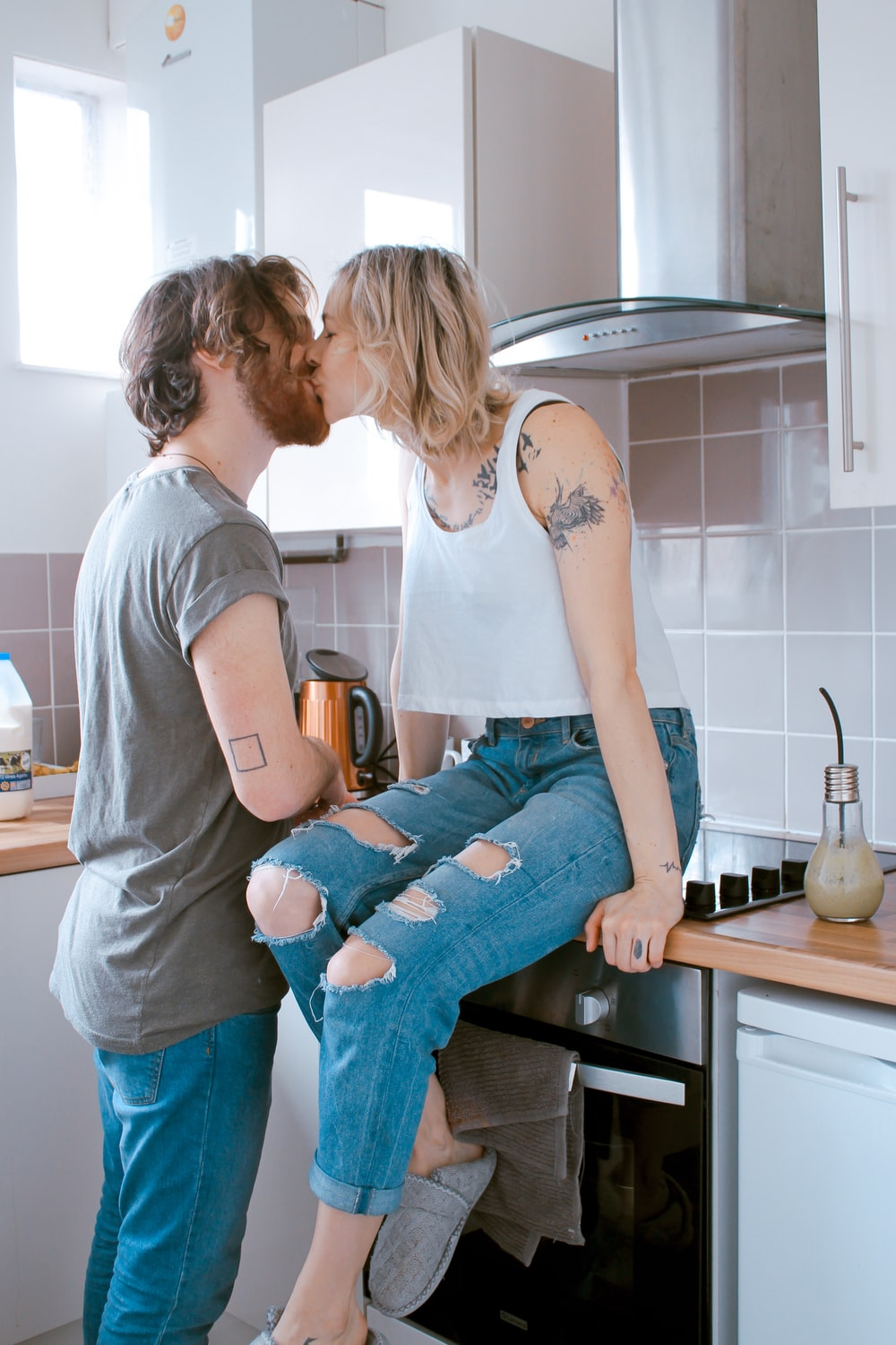 man and woman kissing inside kitchen