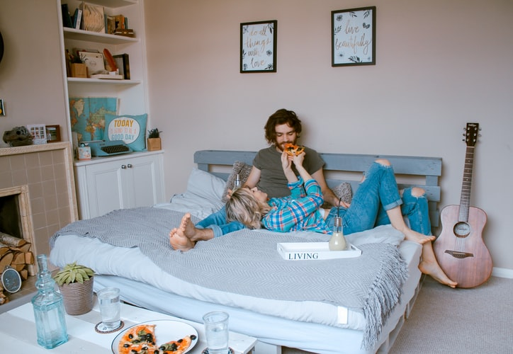 man and woman lying on bed, relaxing, dating.