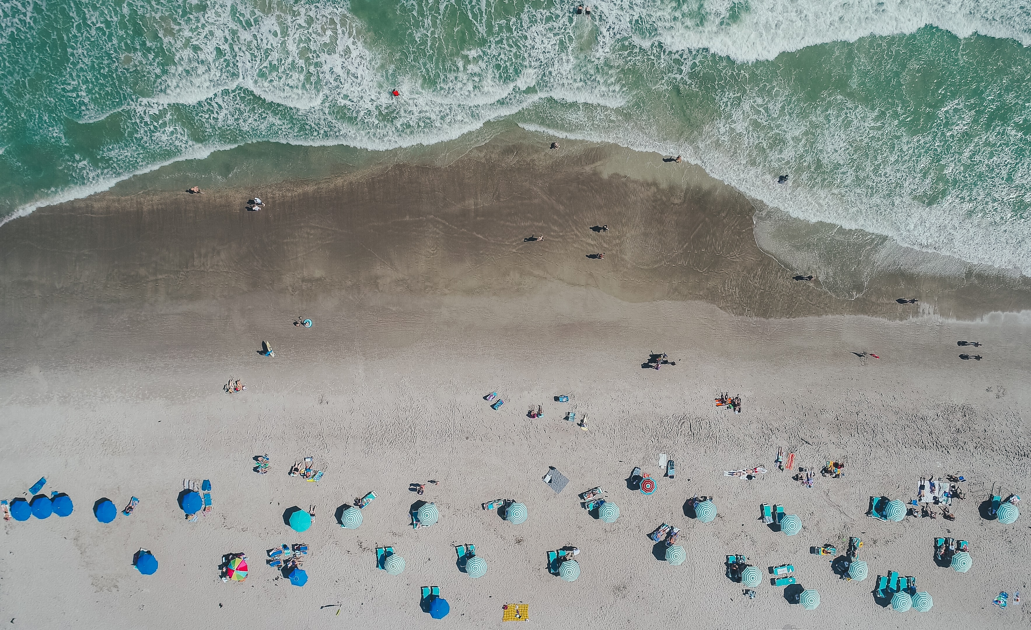 An aerial shot of vacationers on a sandy beach with blue umbrellas and deck chairs