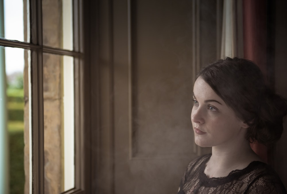 woman standing near window looking outside