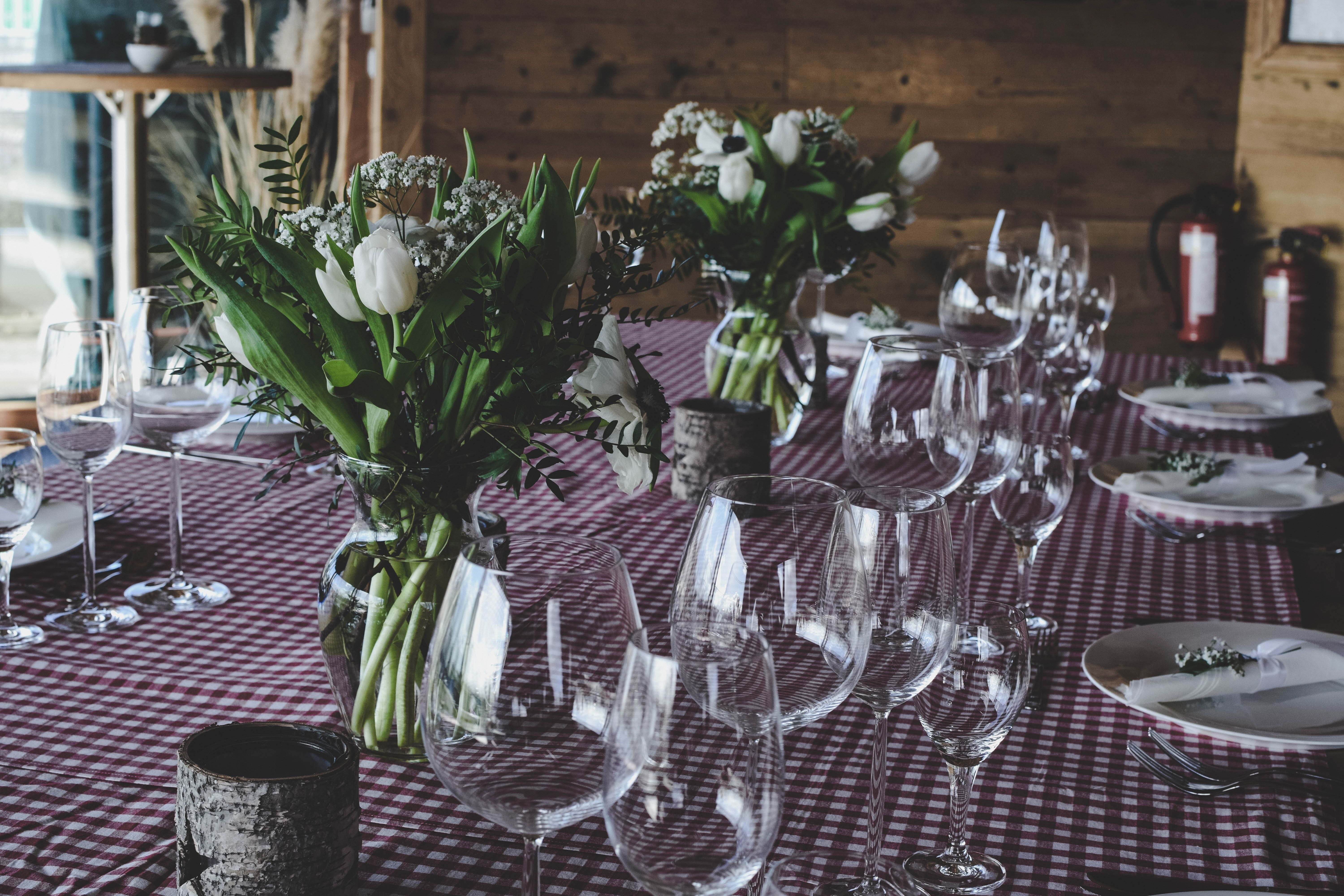 clear wine glasses beside white flower centerpiece on red and white table cover