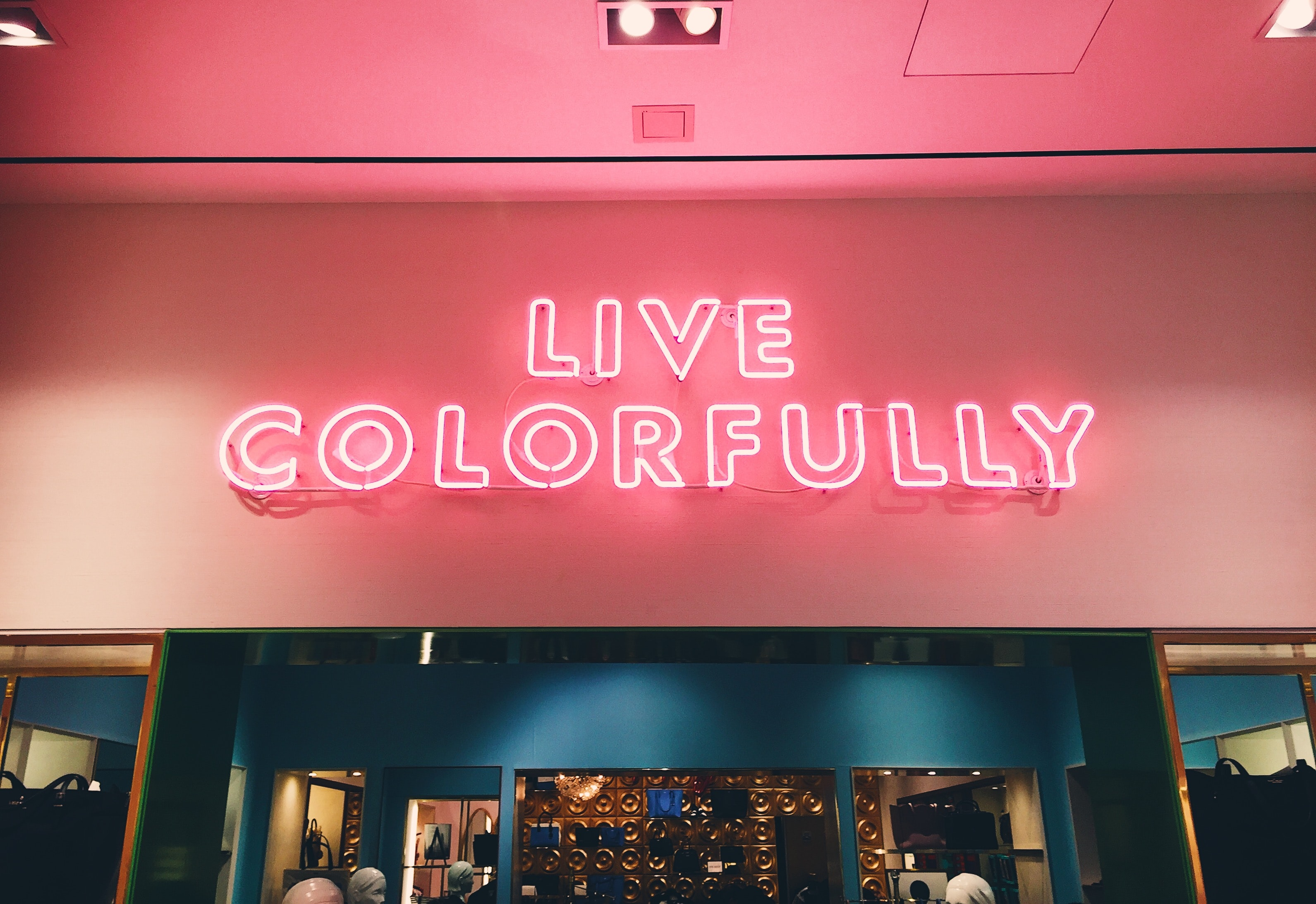"A bright reddish-pink sign that reads ""Live Colorfully."""