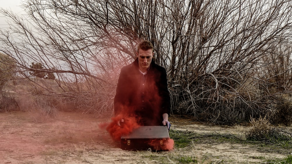 A man opening his suitcase on the ground, as red smoke escapes it.