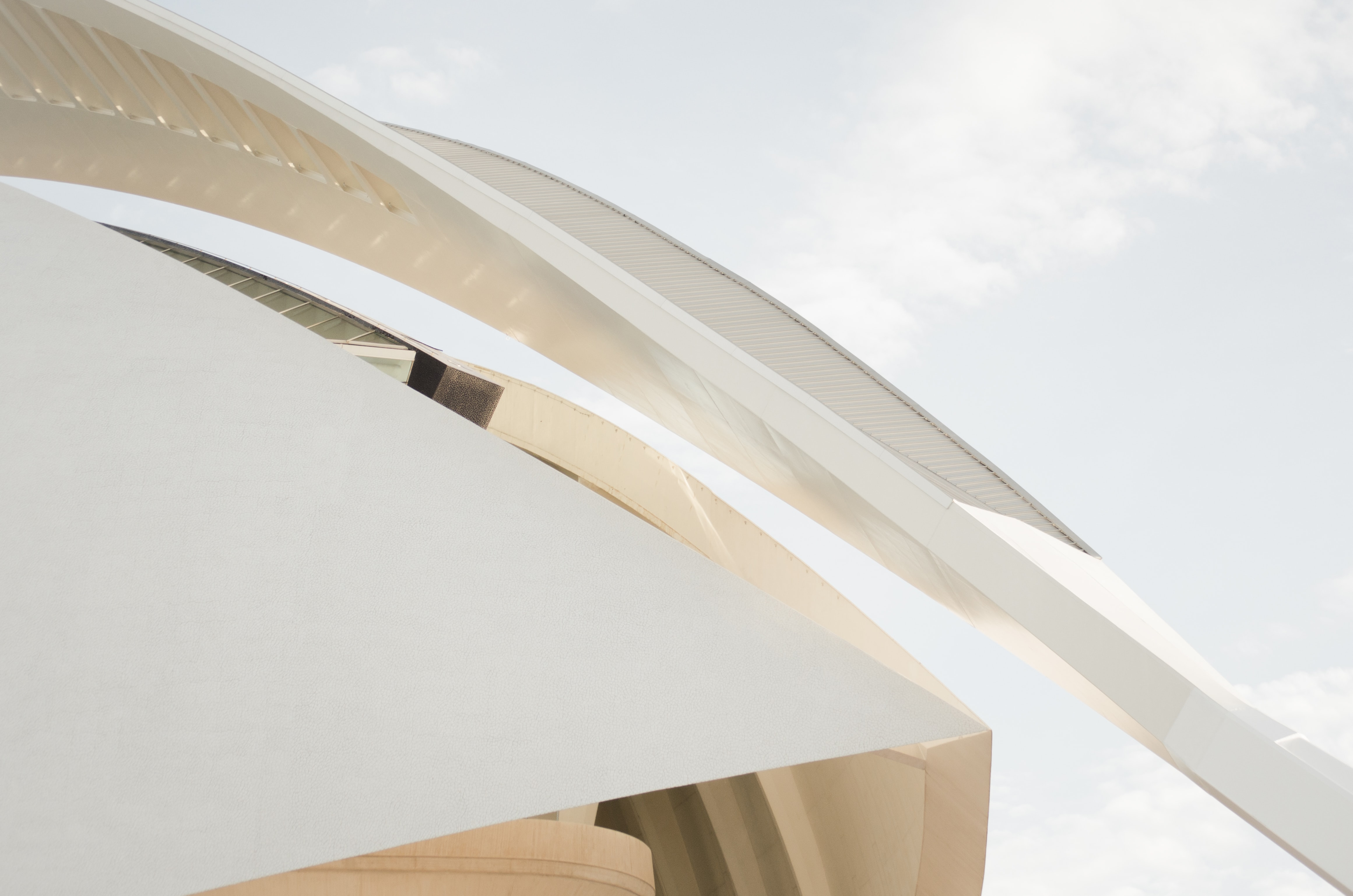 A long arch at the edge of a modern white facade