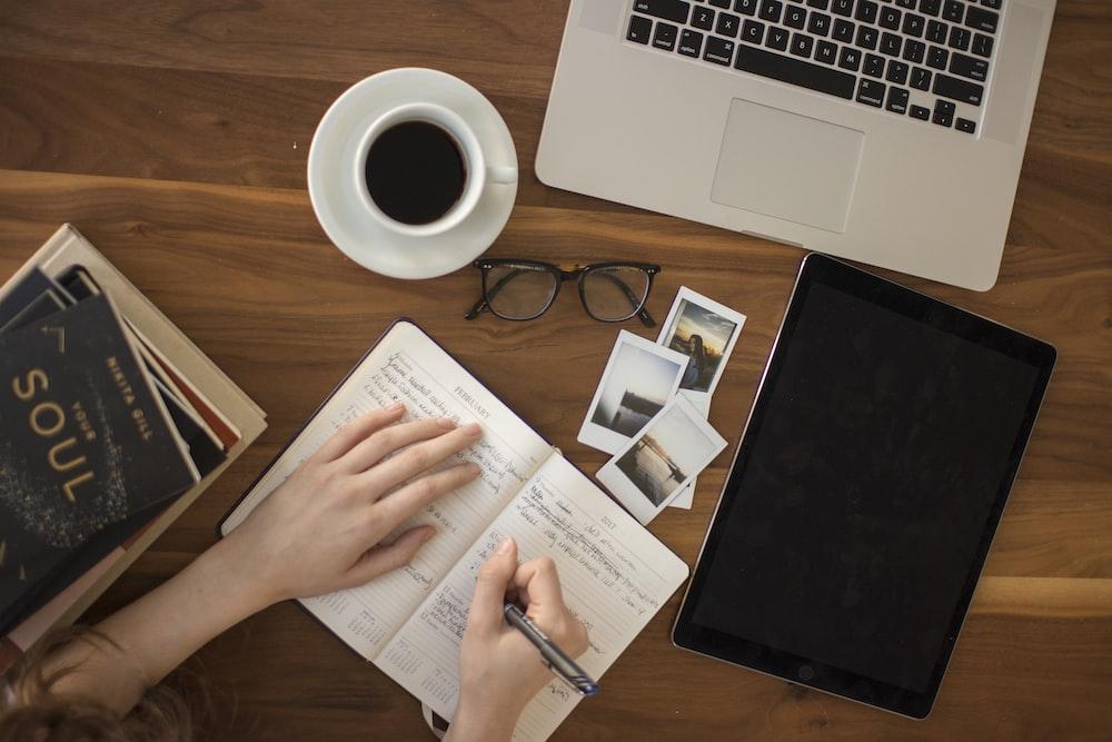 osoba posiadająca długopis pisania na notebooku - kursy online
