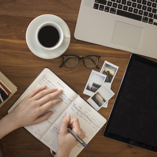 person writing in a notebook beside by an iPad, laptop, printed photos, spectacles, and a cup of coffee on a saucer