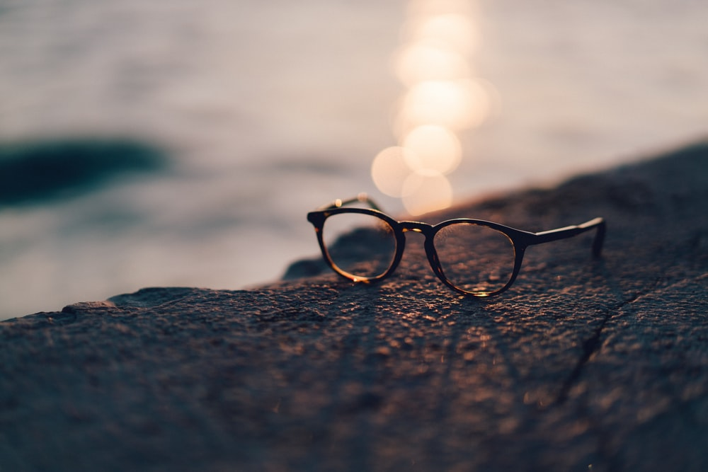 close-up photography of black framed clear lens sunglasses near body of water