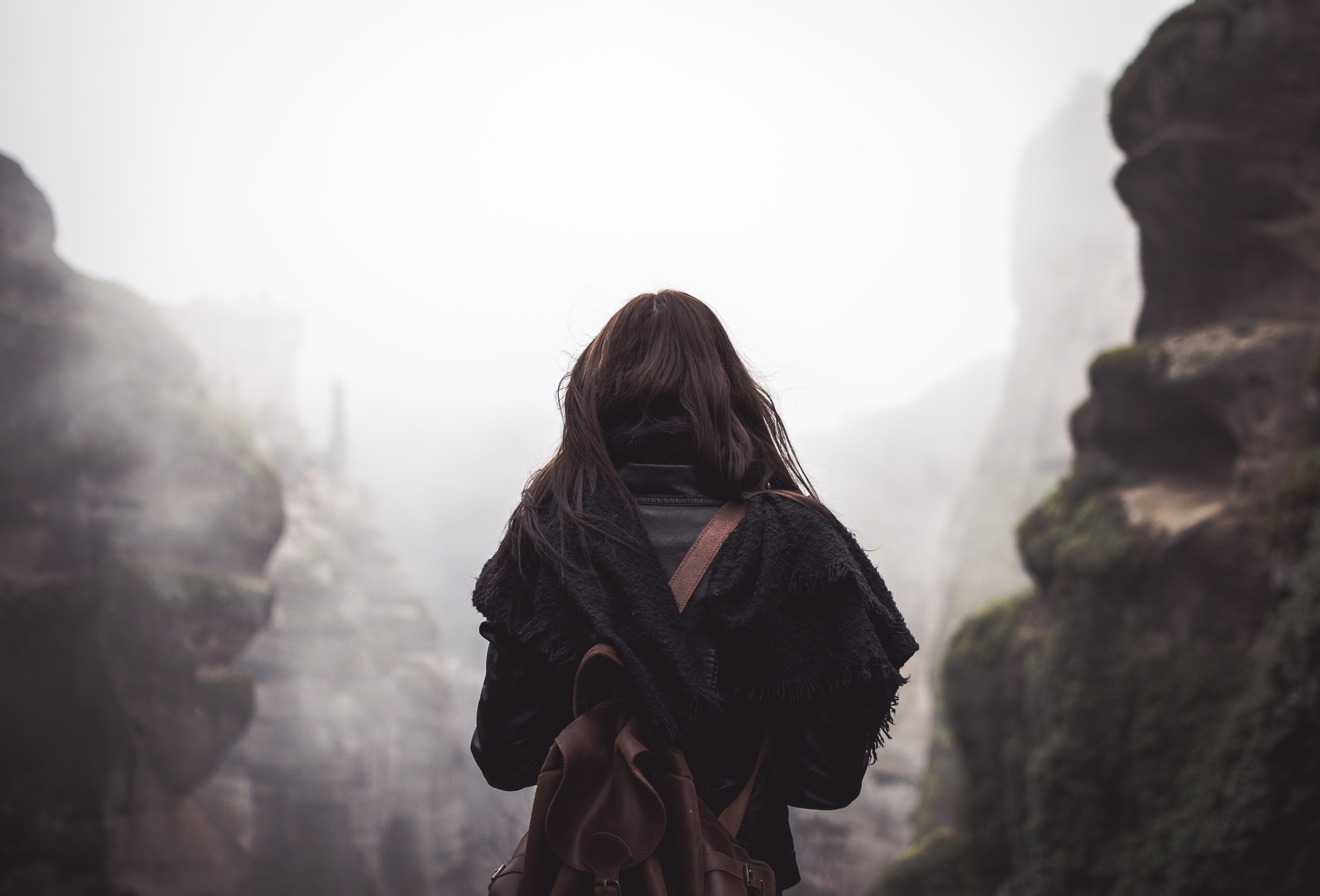 Woman in a scarf and backpack standing between foggy mountains