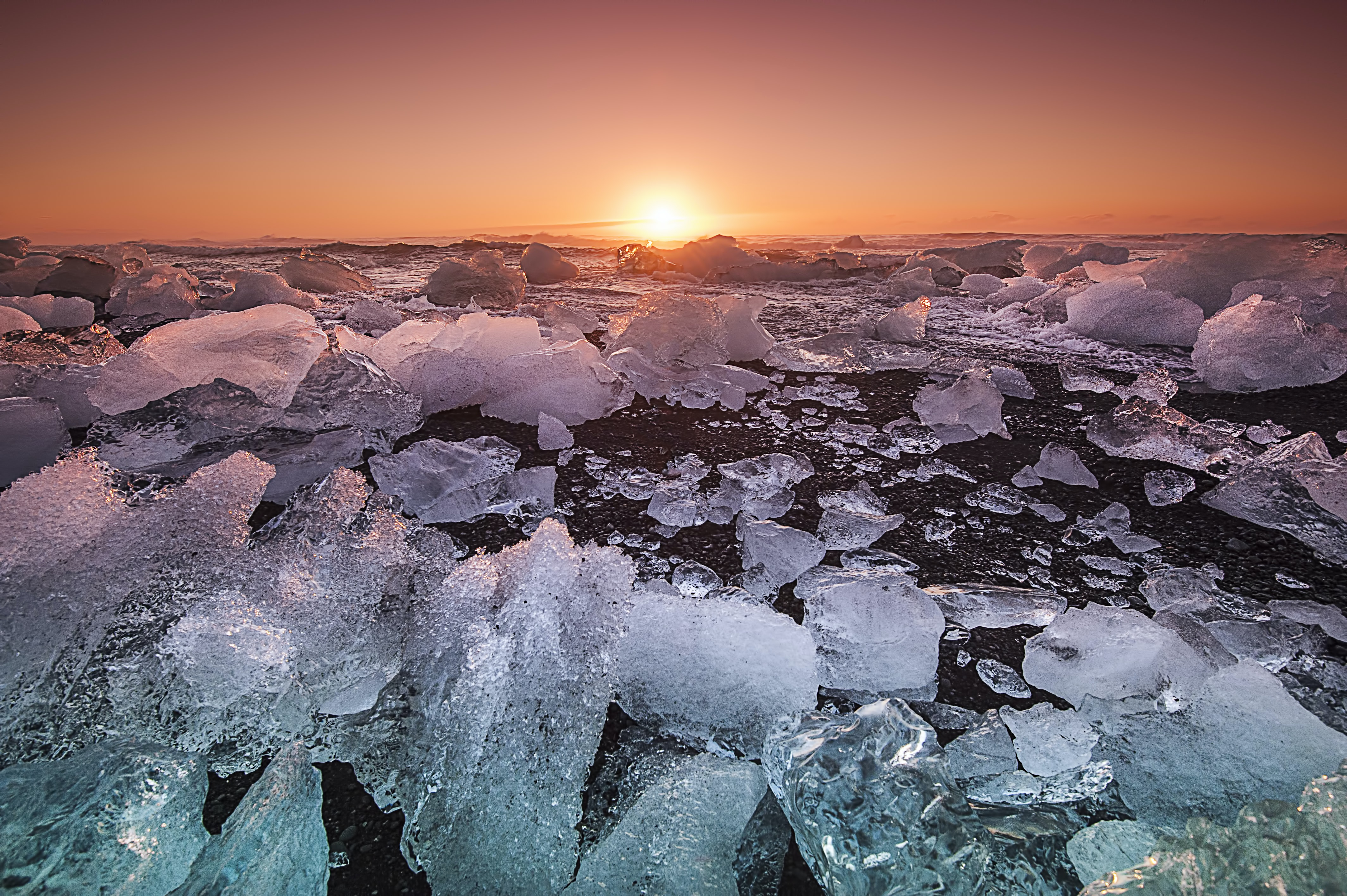 Ice breaks up on the shoreline at sunset against an orange sky and calm water in Iceland.