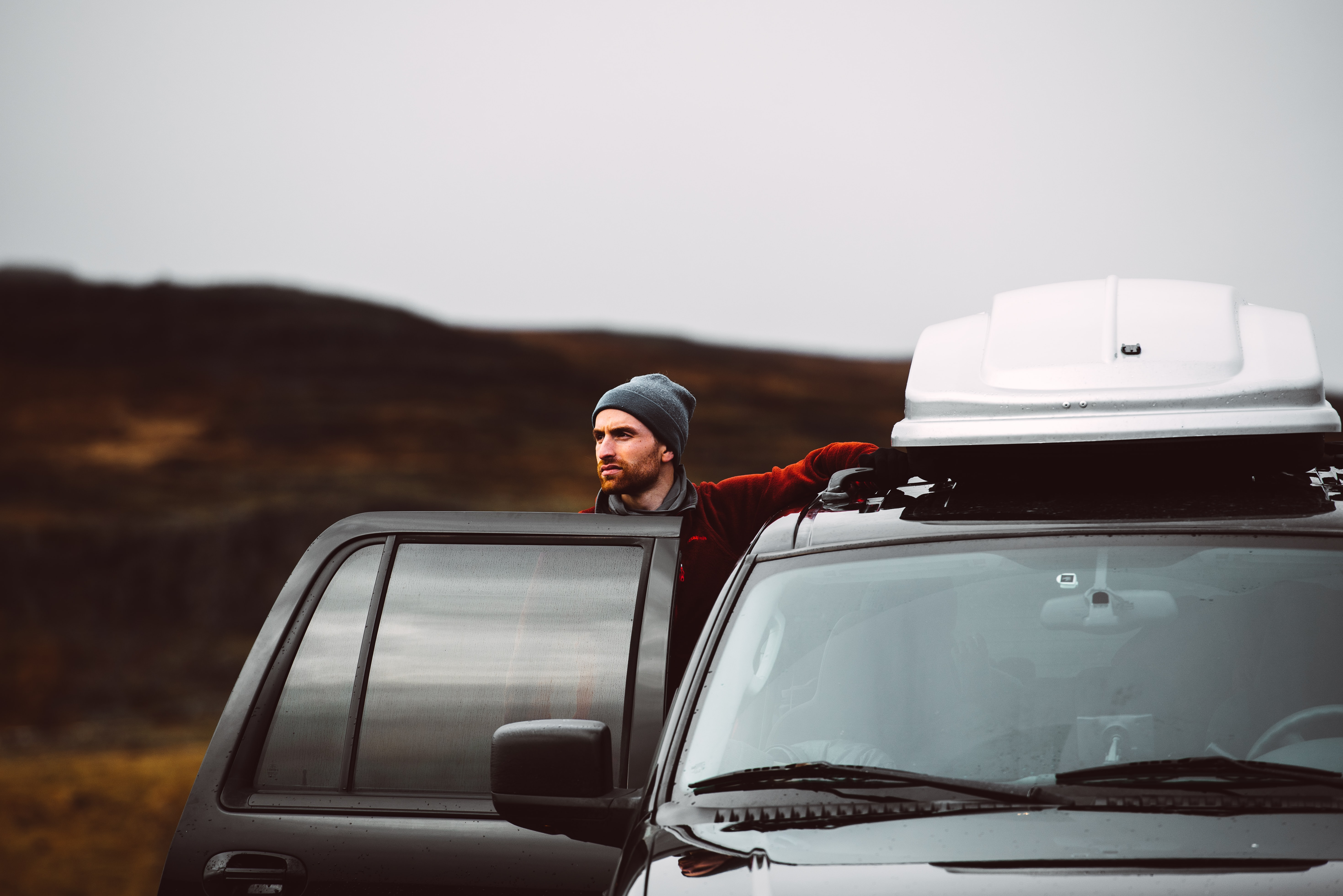 A bearded man in a beanie stepping outside his car in the Icelandic wilderness