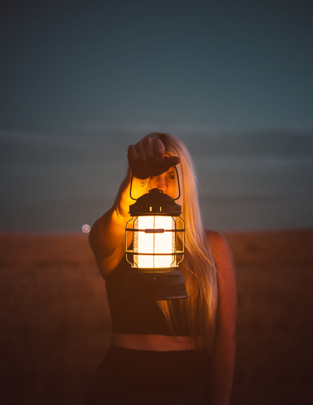 shallow focus photography of woman holding lantern
