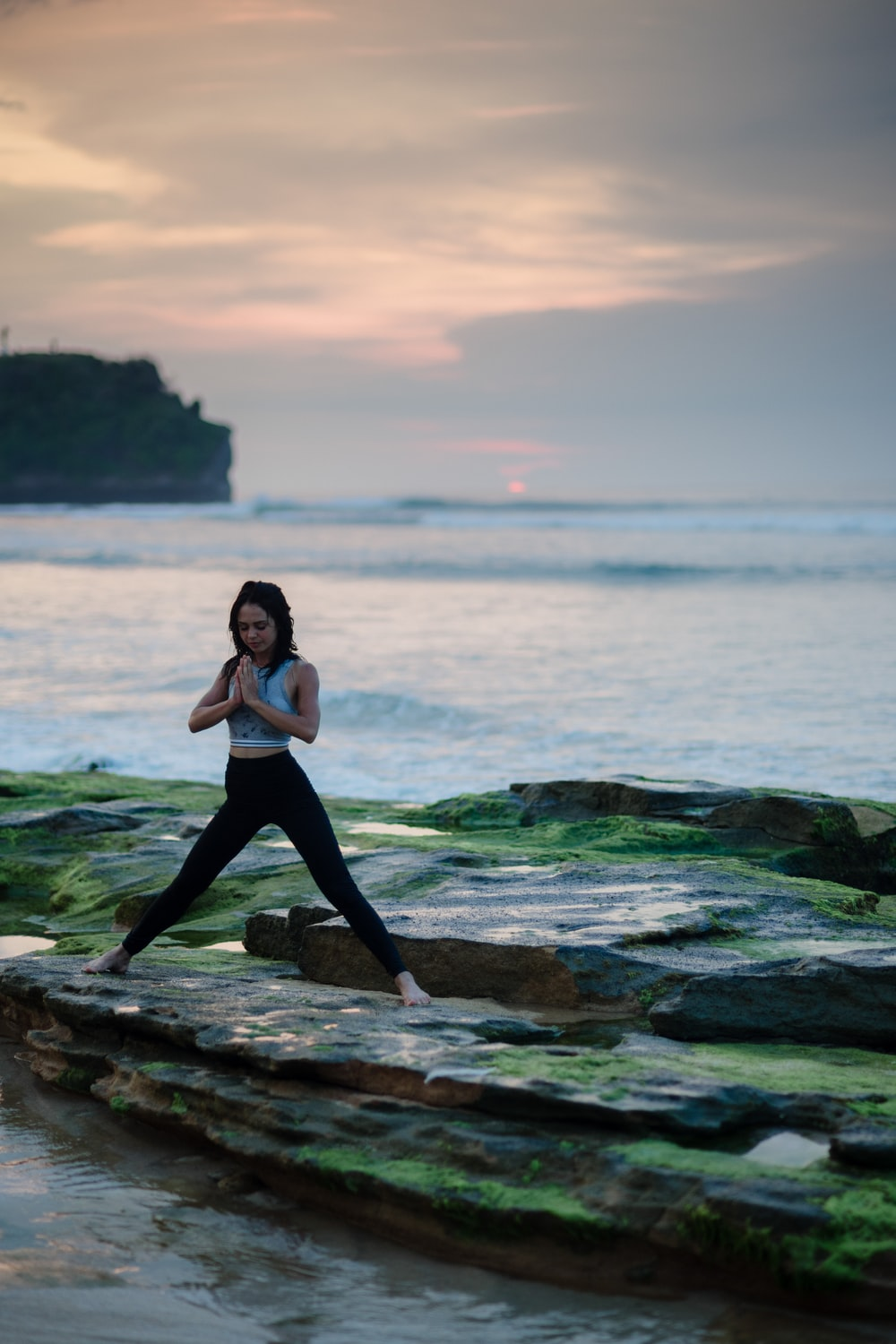 woman doing yoga on rock platform next to body of water