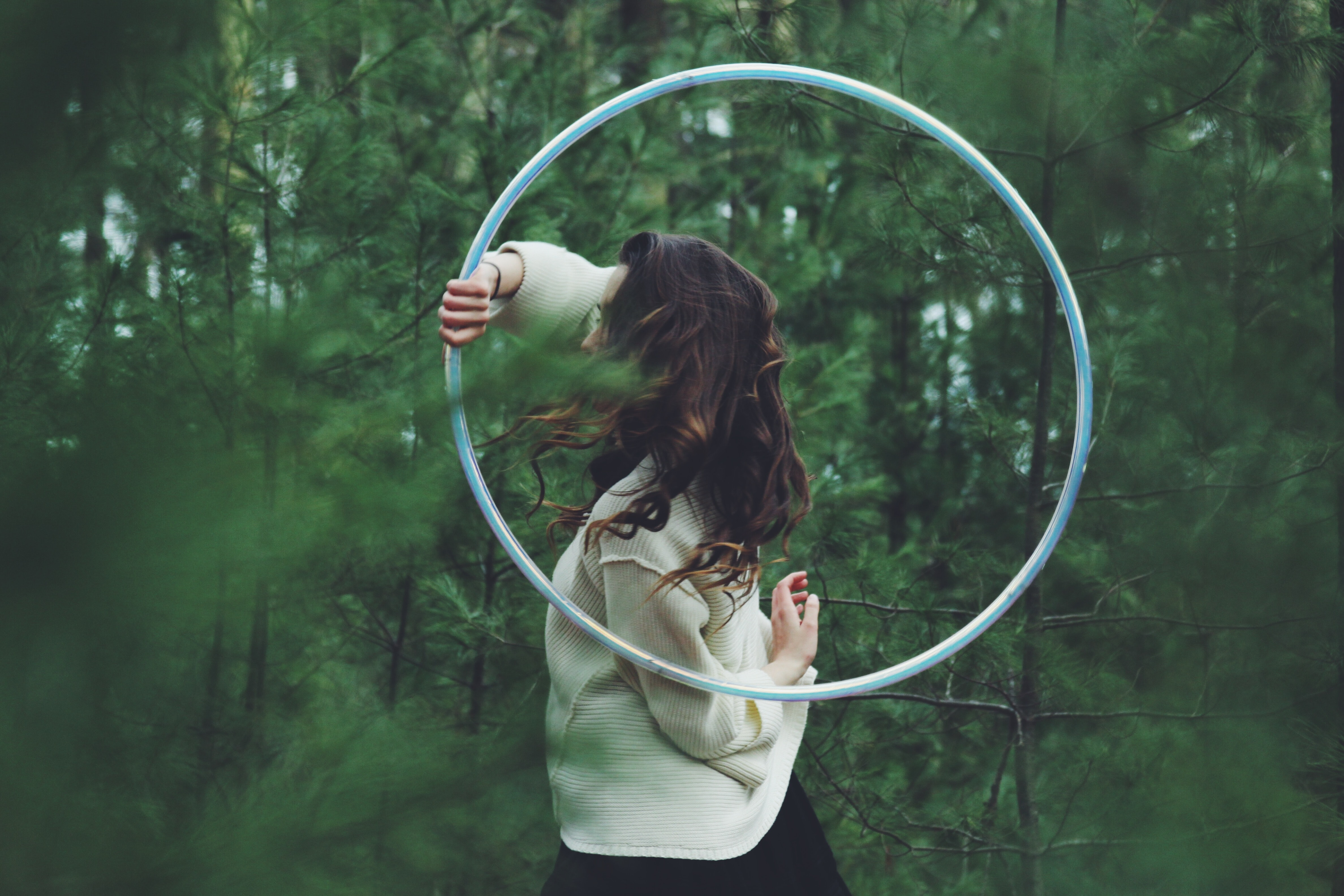 A woman with a hula hoop in a dense forest