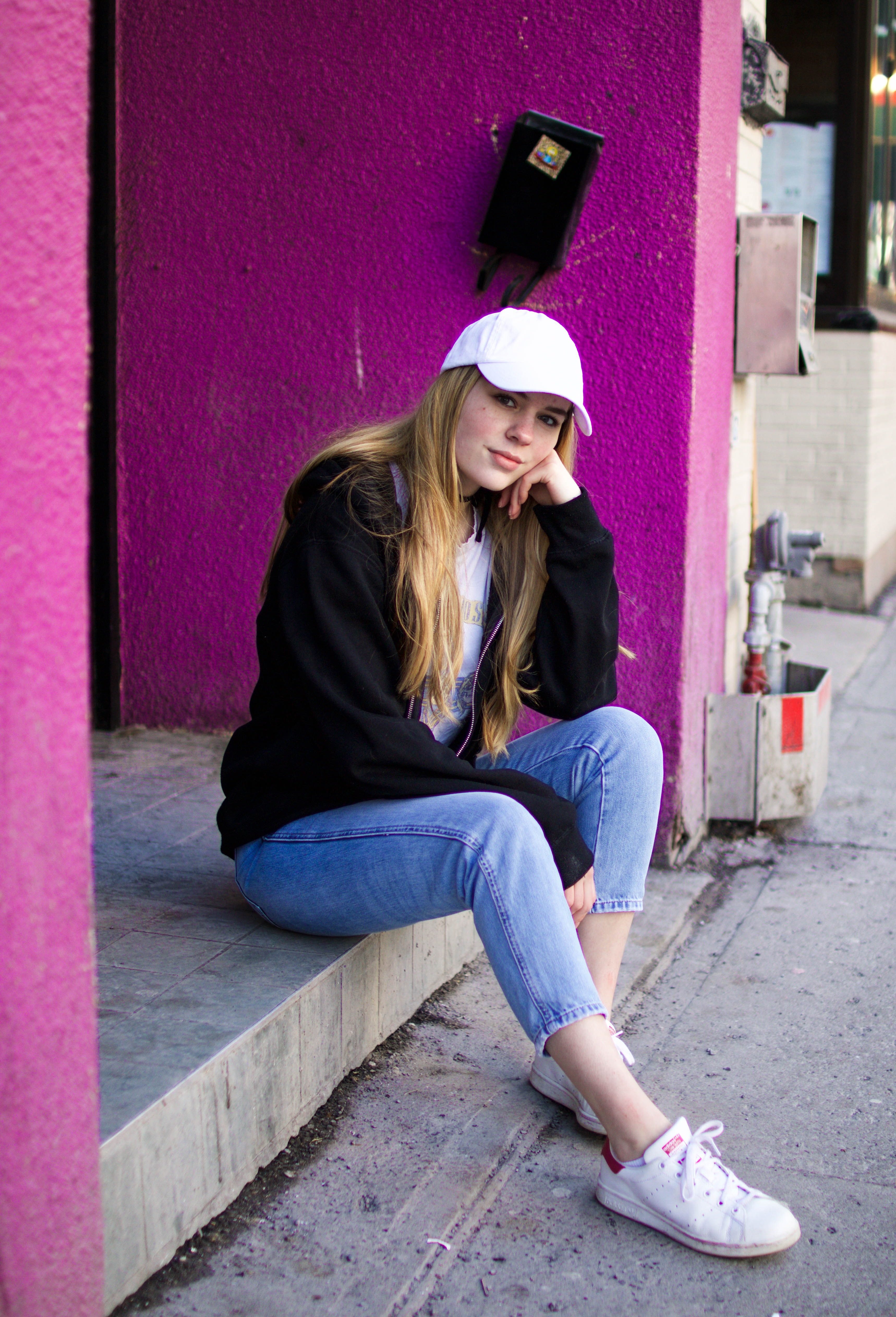 A pretty blonde woman sitting on a step outside with her hand against her cheek.