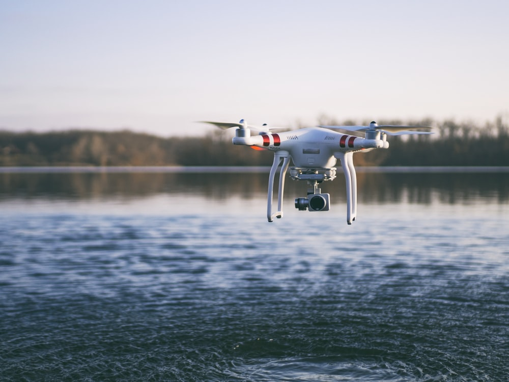 white quadcopter drone flying above body of water