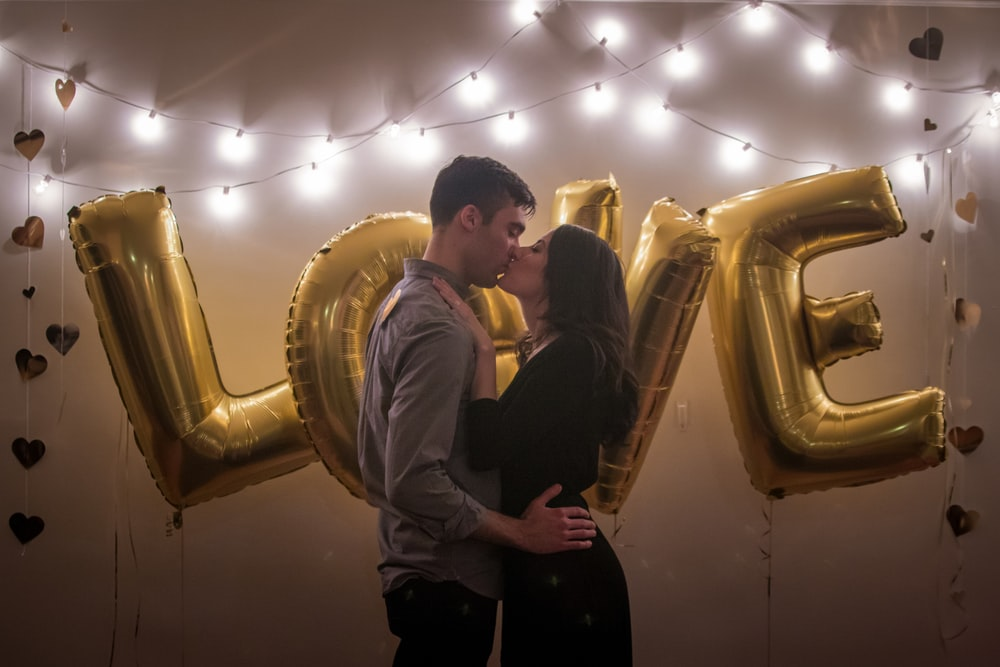 "A couple kissing in front of gold colored balloons that spell out ""Love."""
