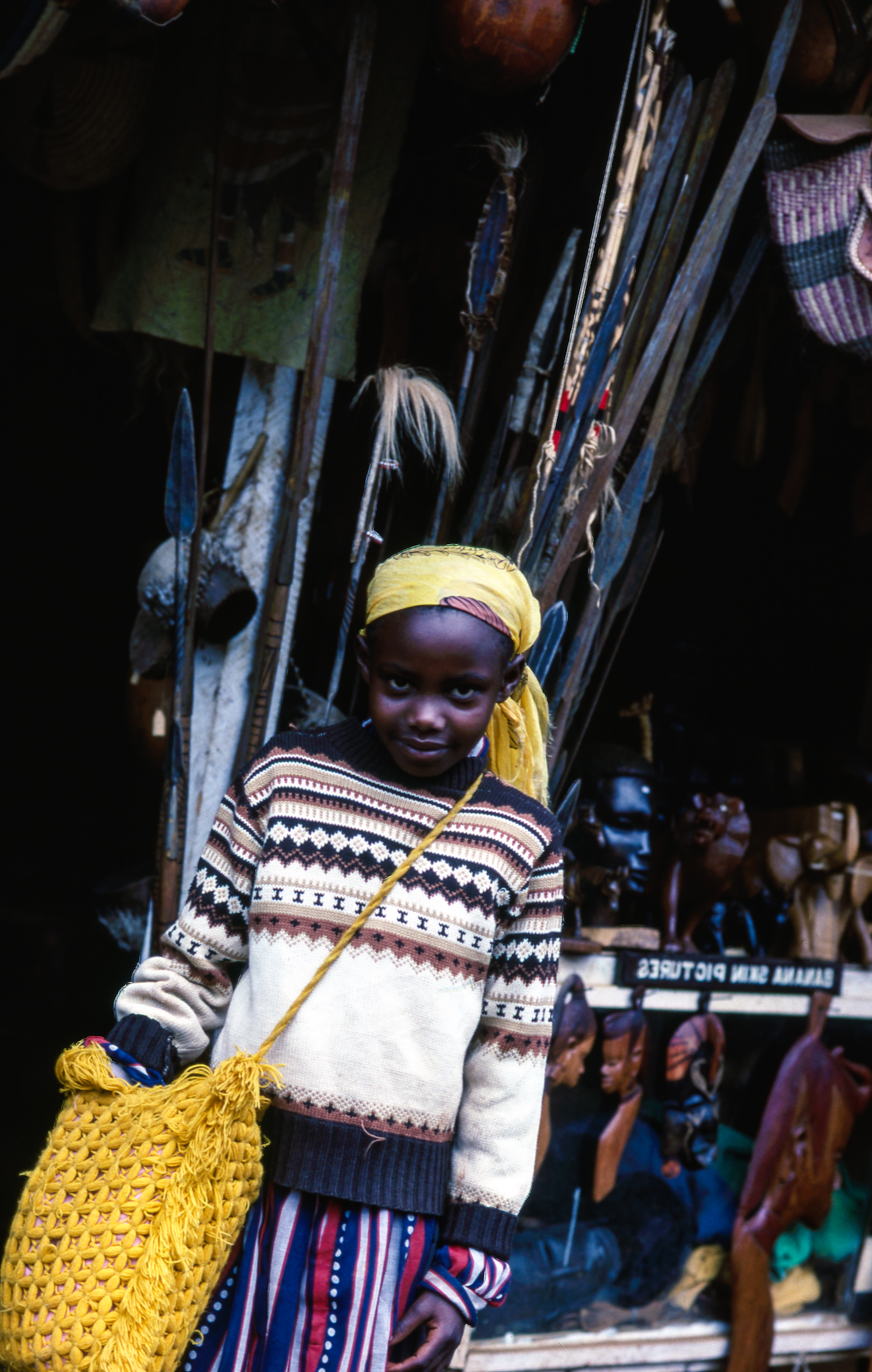 Child in a colorful outfit with a yellow bag at an outdoor market