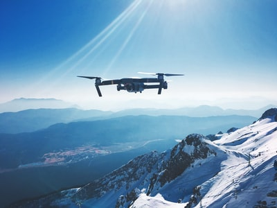 white quadcopter drone flying near snow mountain during daytime drone teams background