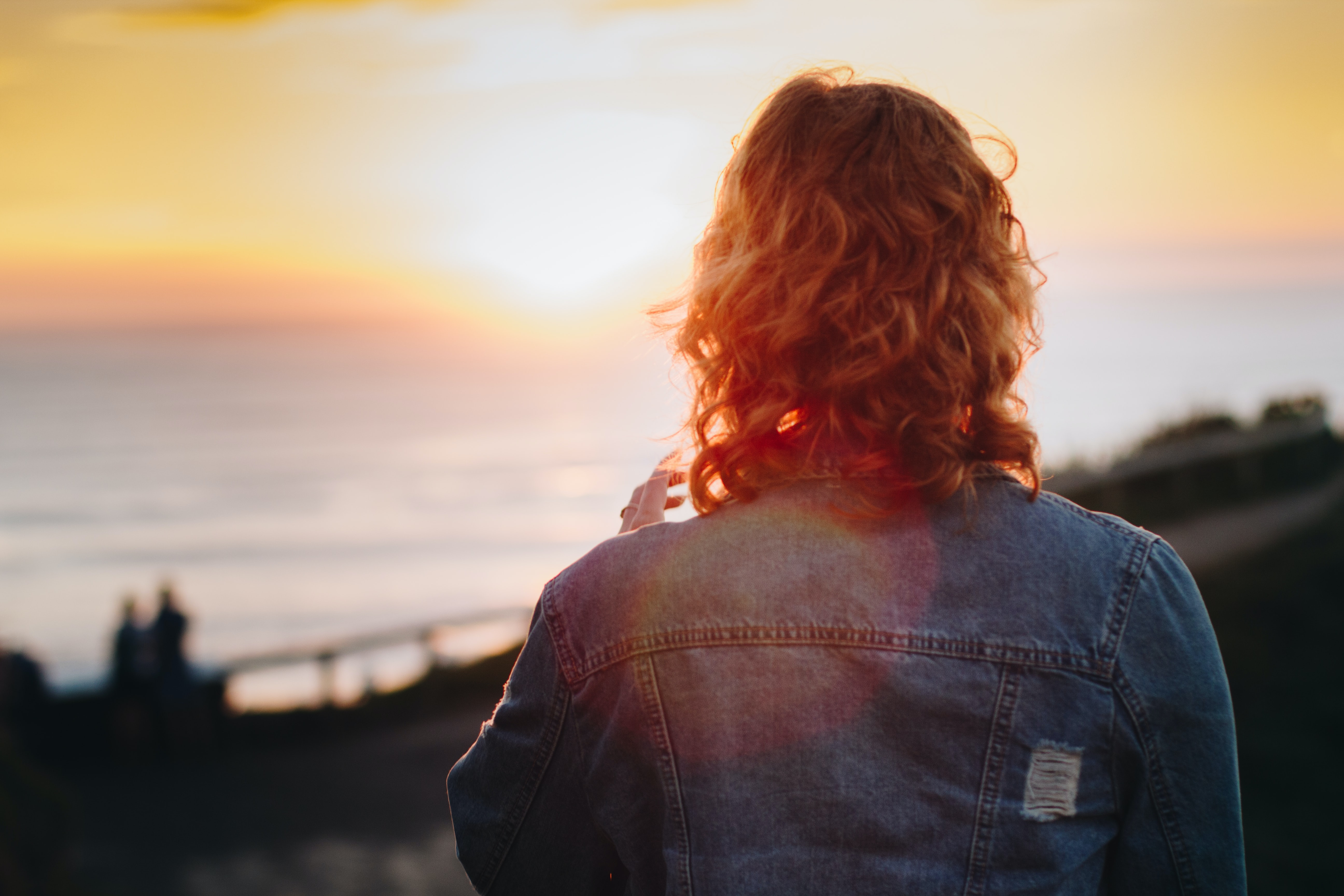 A person with long, curly hair and a denim jacket faces the obscure coastal view and sunrise-or-sunset horizon