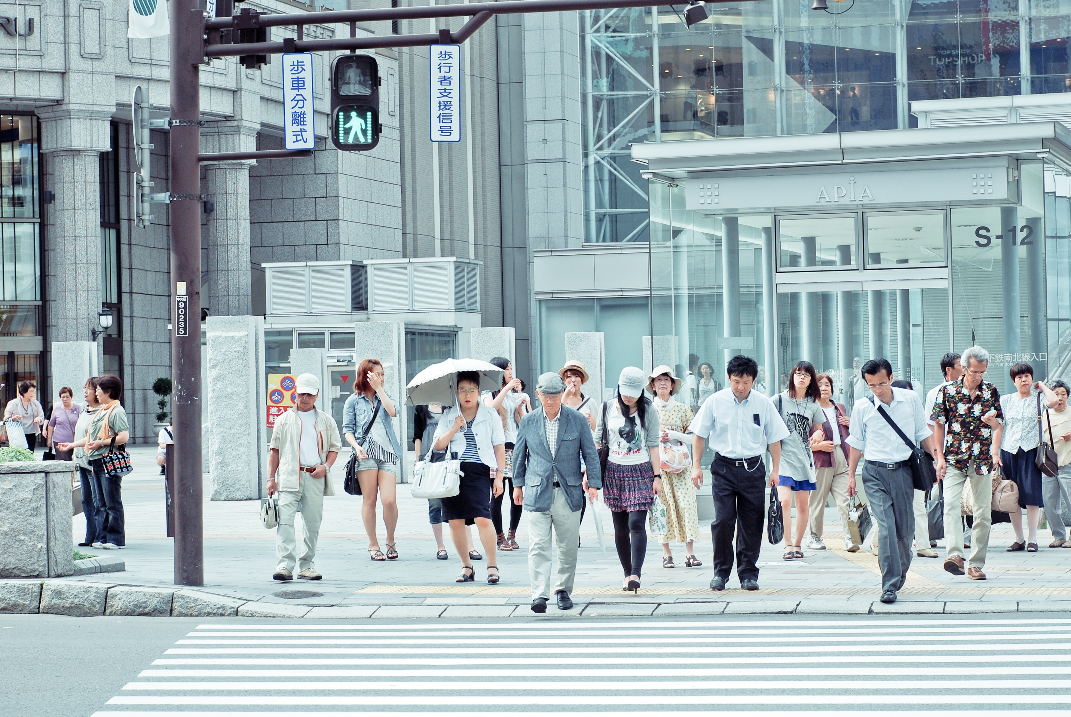 Pedestrians waiting to cross a street in Sapporo
