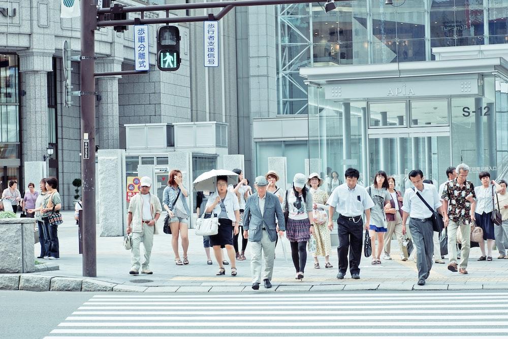 people crossing pedestrian lane near building at daytime