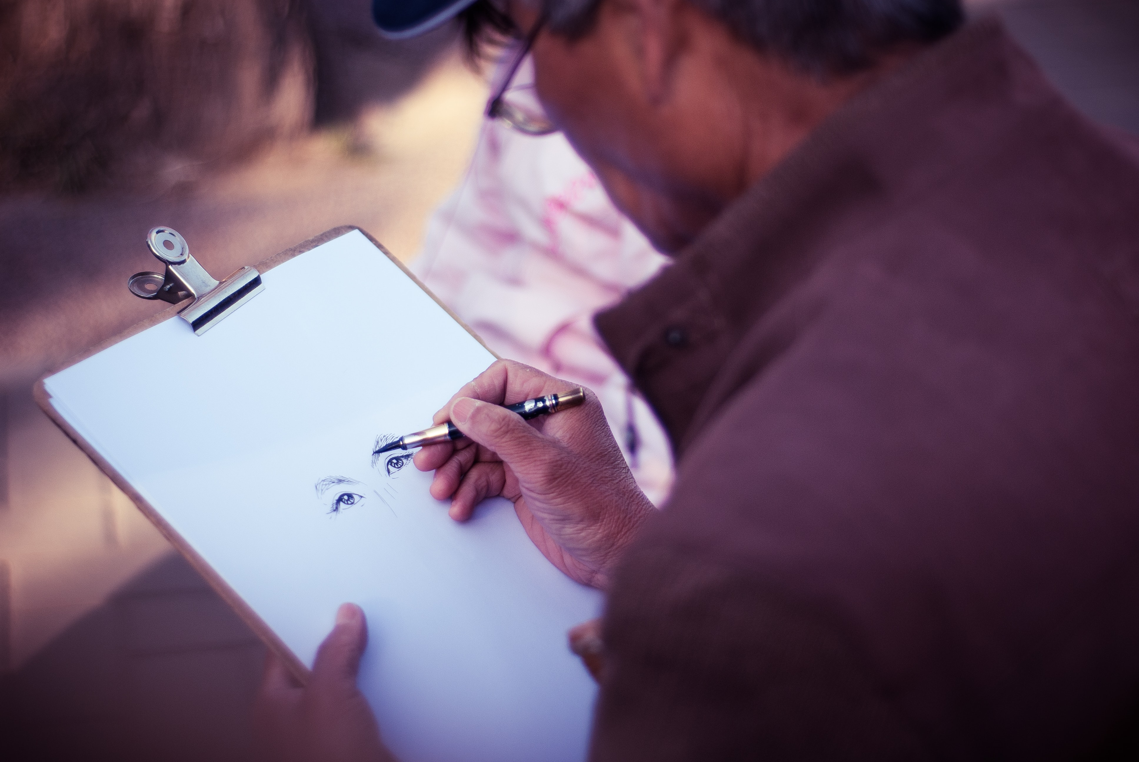 Close up of illustrator in glasses holding clipboard drawing face in Beihai Park