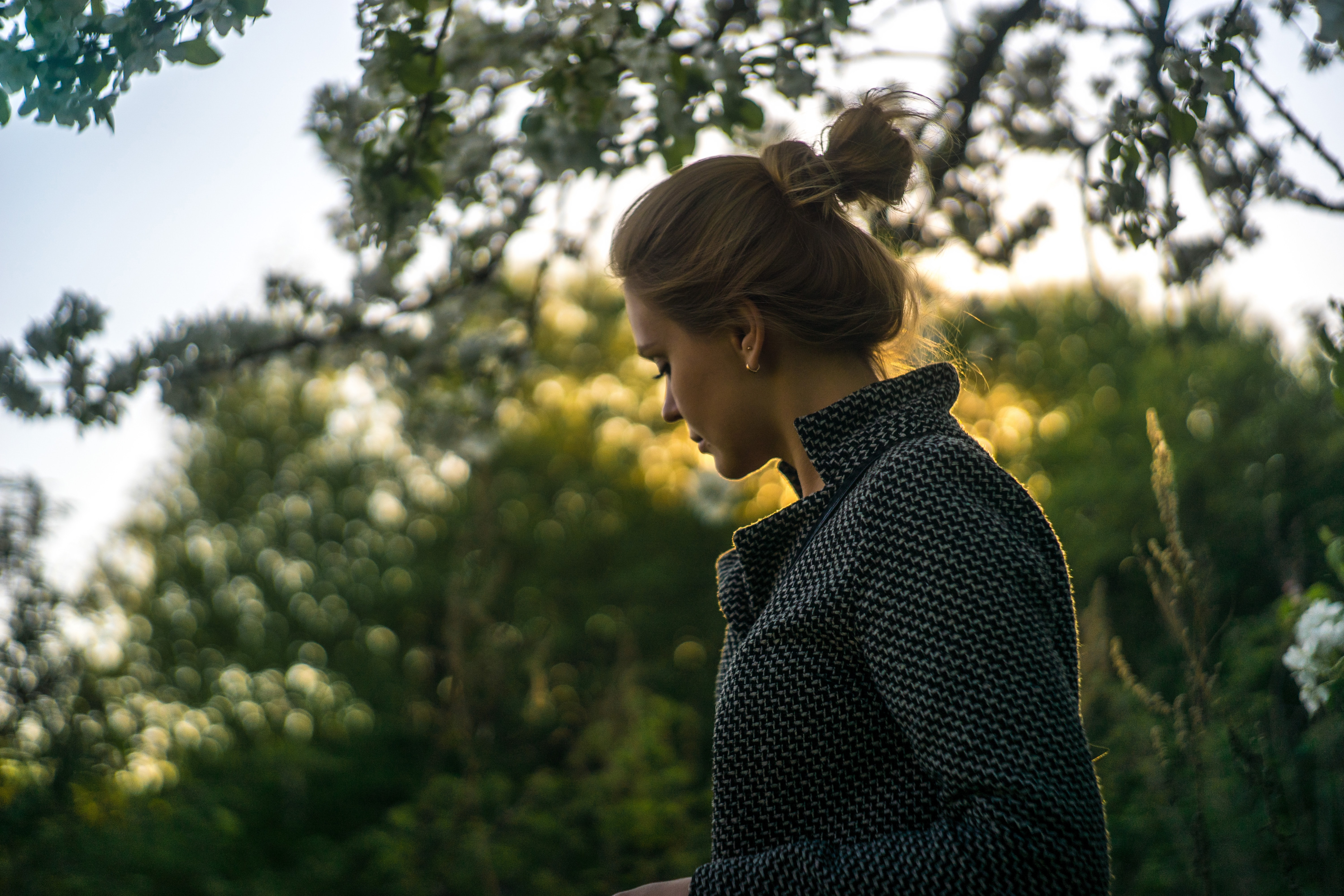 A woman with a bun wearing a coat looks down against a background of trees
