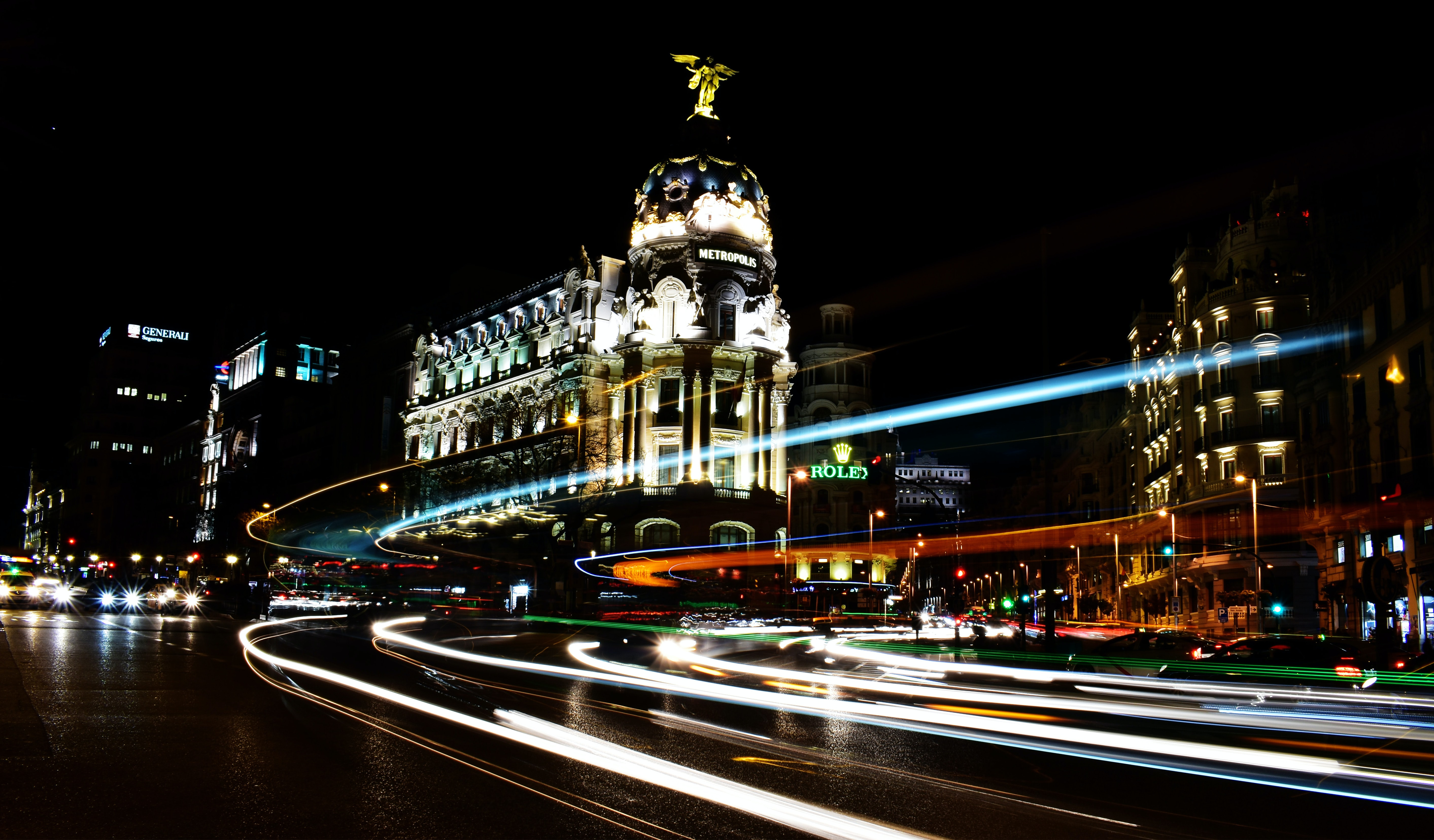 A dark shot of urban buildings lit up at night in Madrid