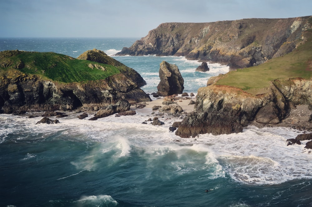photo of sea waves and boulders