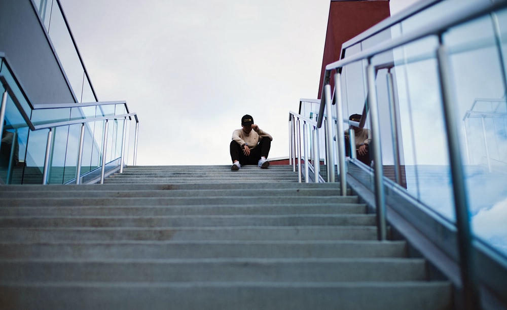 worm's eye view of man sitting on staircase