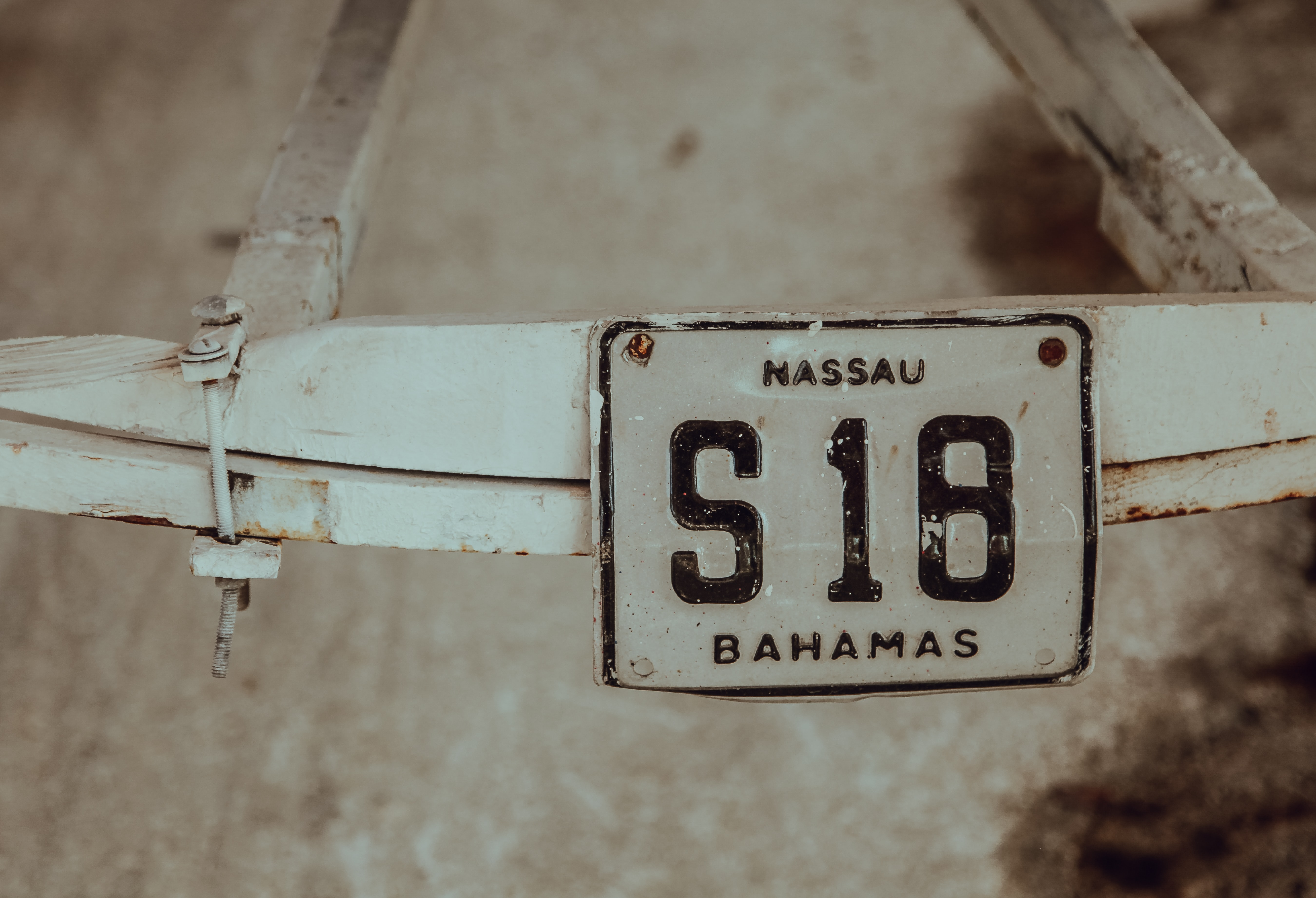 shallow focus photography of white Massau S18 Bahamas license plate mounted on white steel frame