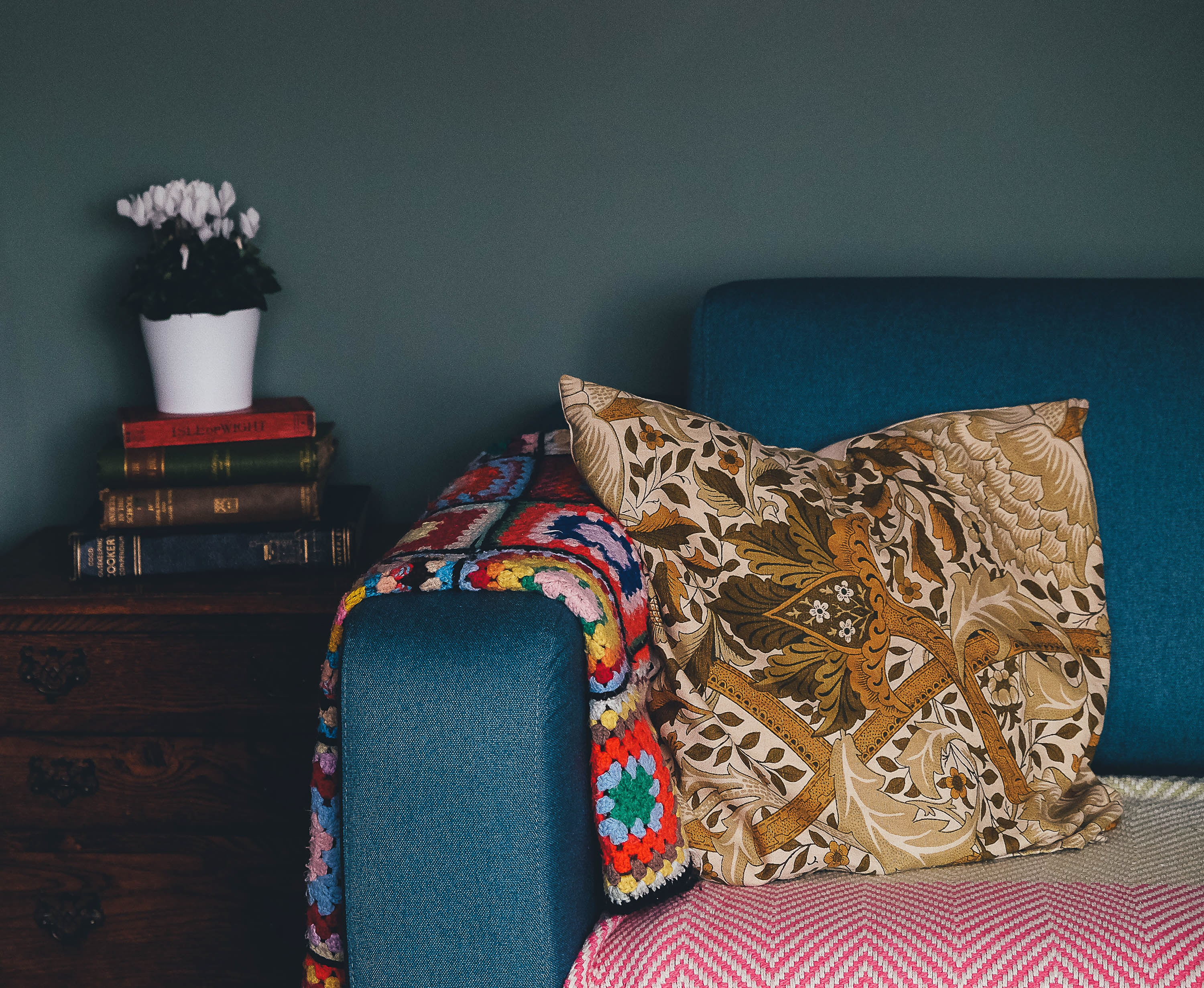 A blue sofa, colored blankets, brown patterned pillow, wooden end table, stack of books, and potted plant in a living room