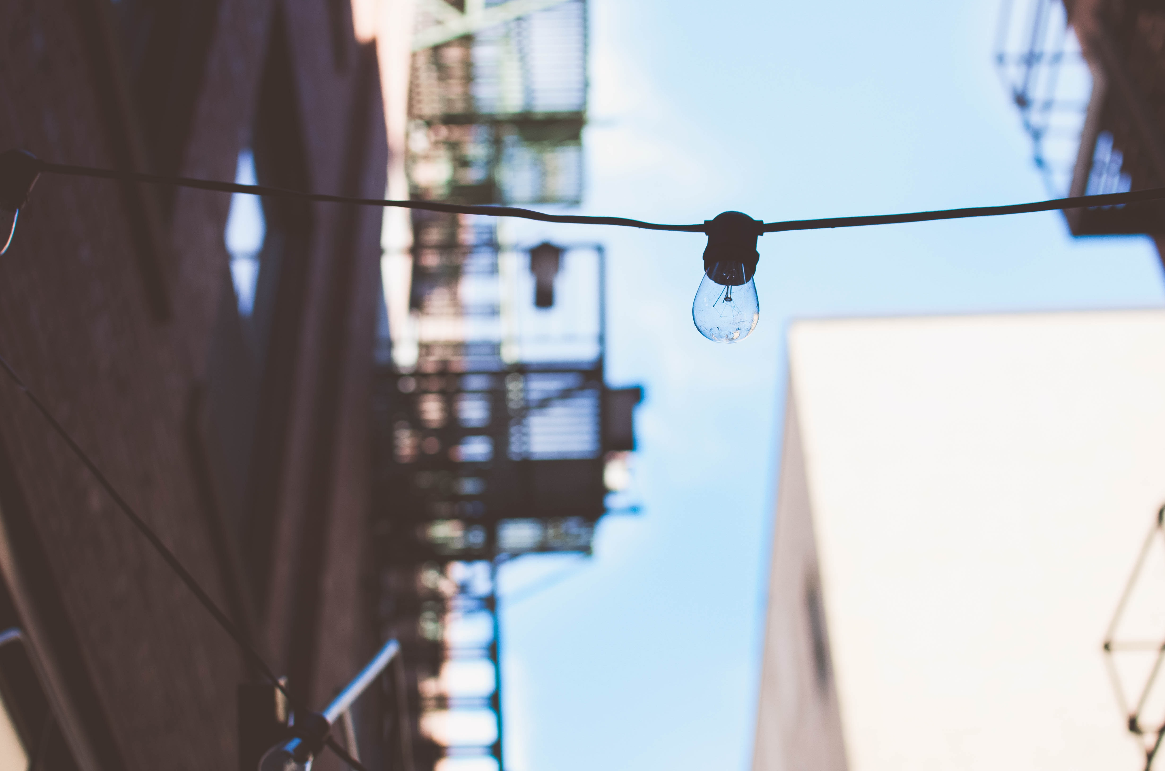 A lightbulb hangs on a cable running between two buildings against a blue sky