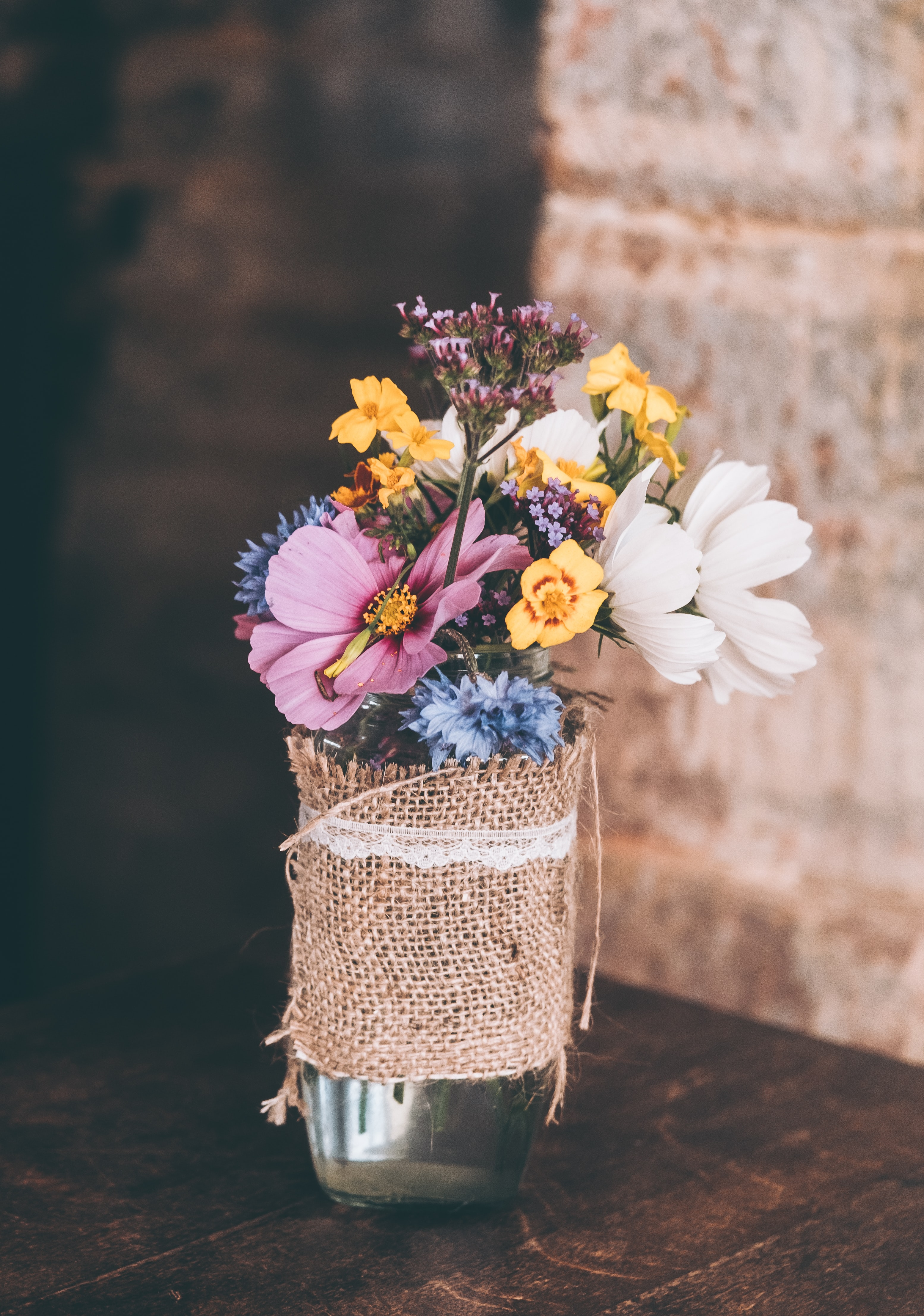 A bouquet of various flowers in a glass vase on a wooden surface