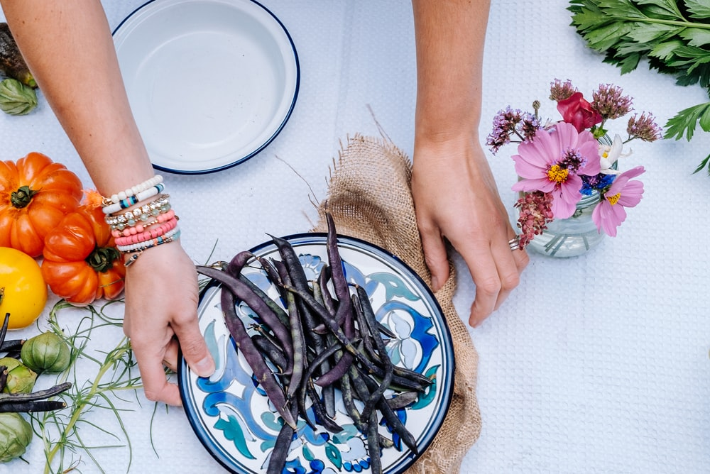 person holding white and blue floral ceramic plate with string beans atop near heirloom tomatoes