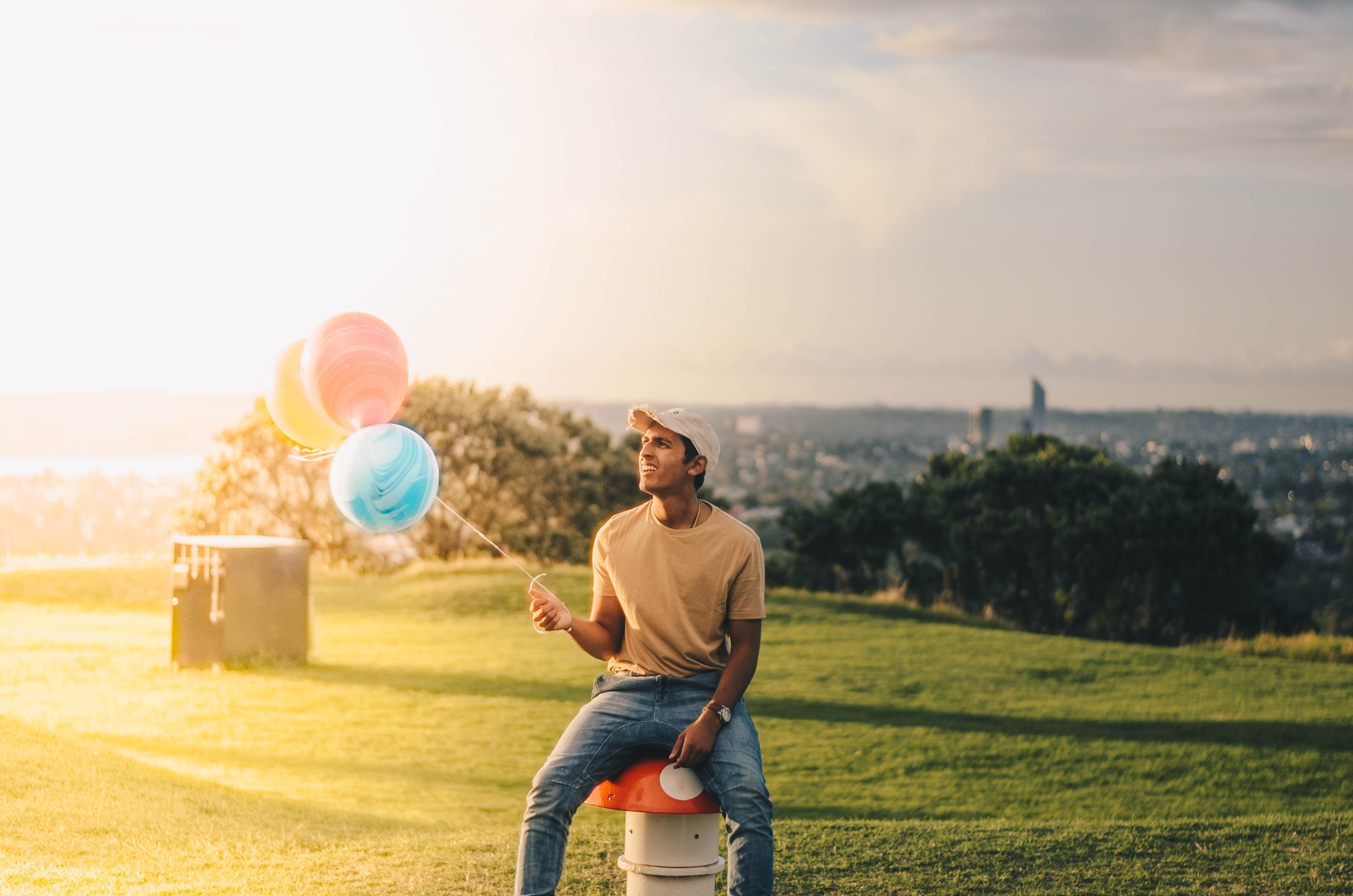 Happy man holding colorful balloons in a sunny field