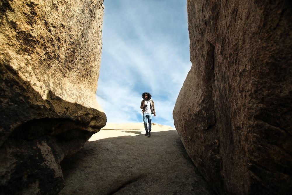 man walking near rock