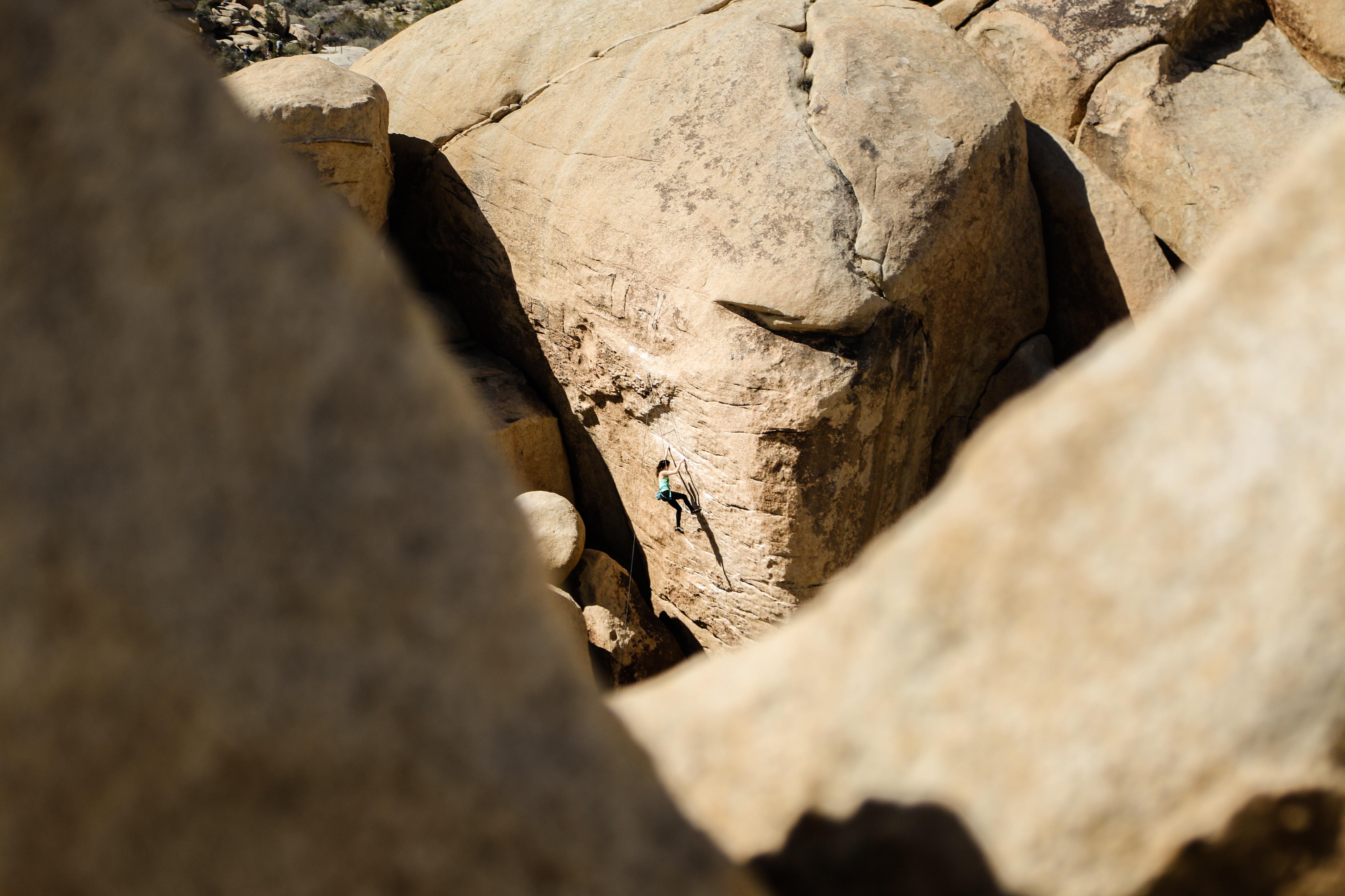 woman climbing on brown rock at daytime