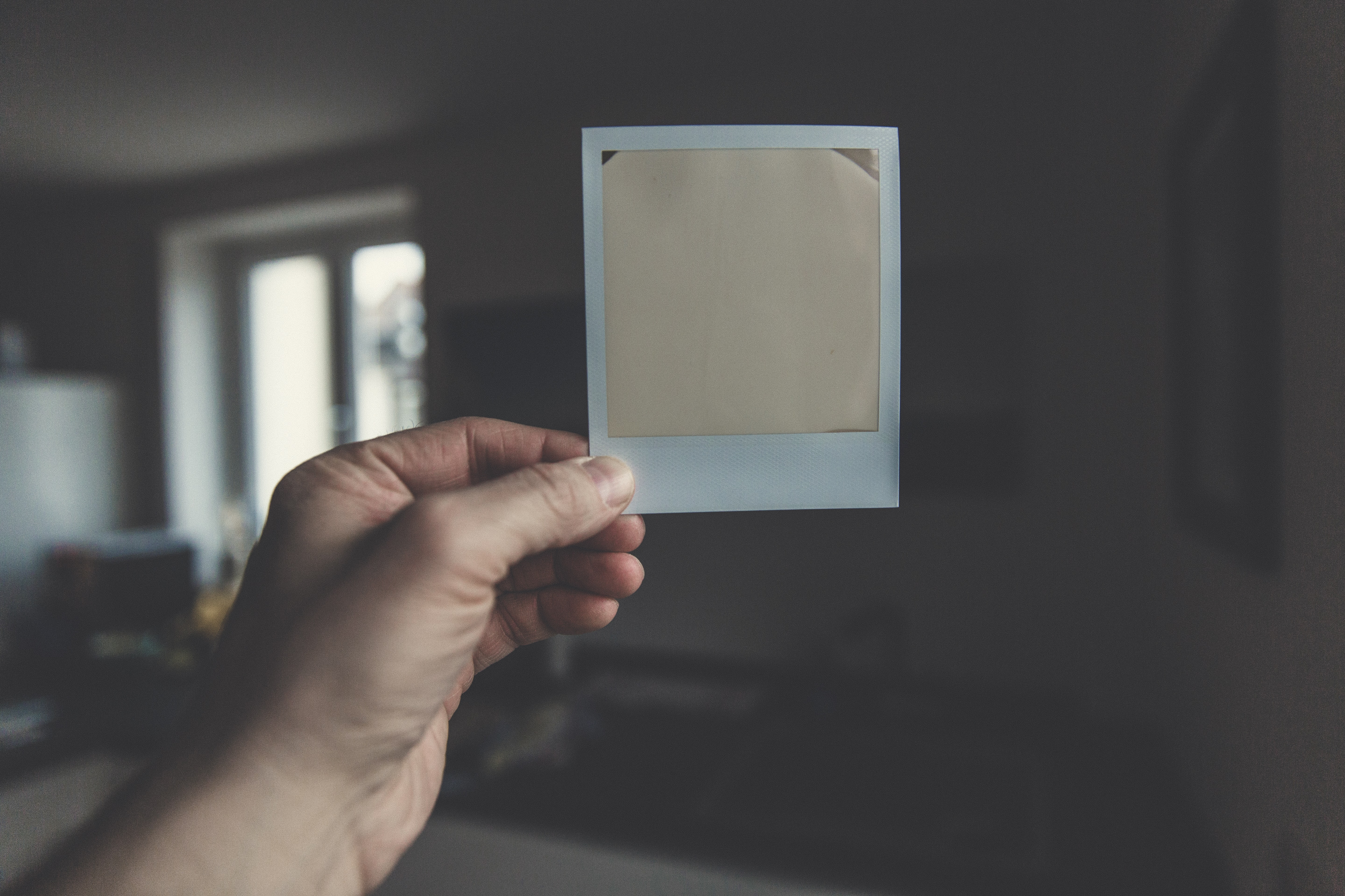 A person holding an exposed piece of Polaroid film in their hand
