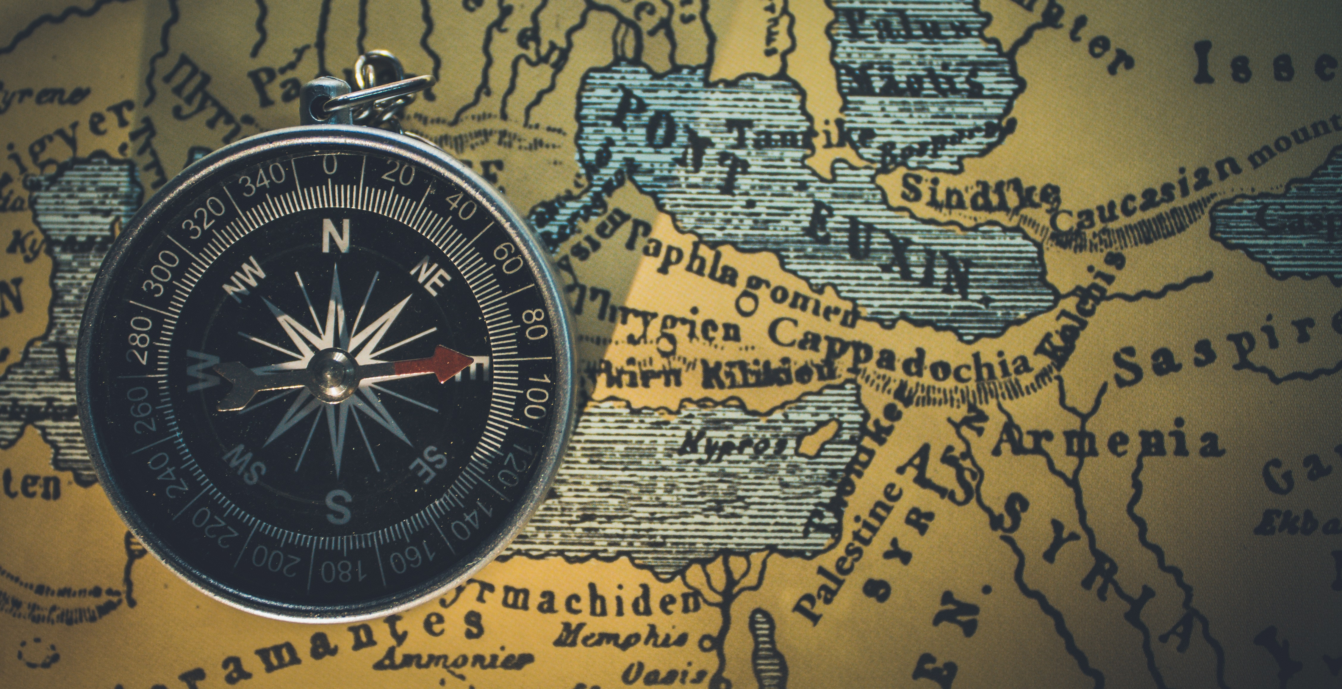 round gray framed compass on brown map