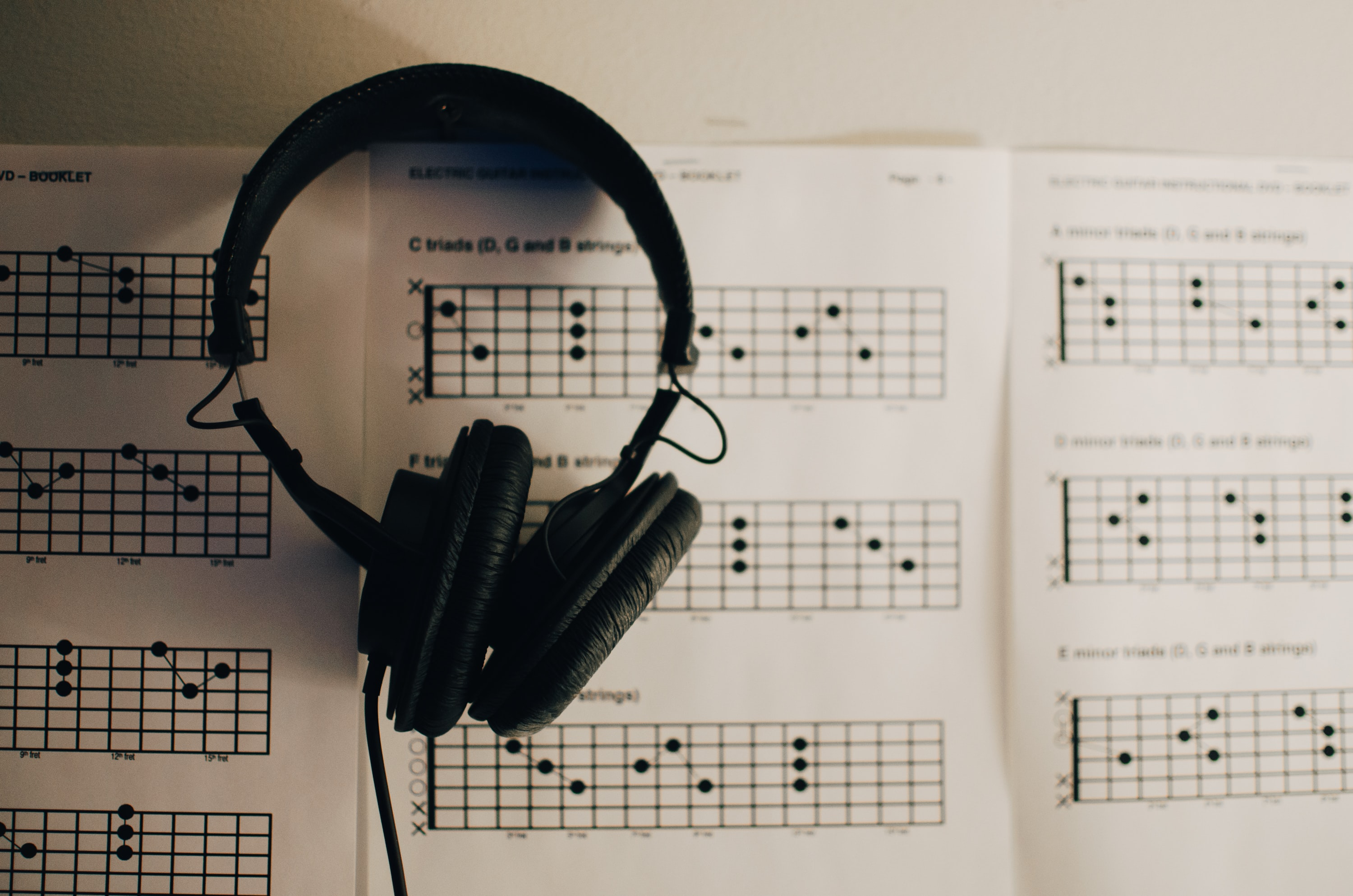An overhead shot of black headphones on guitar chord charts